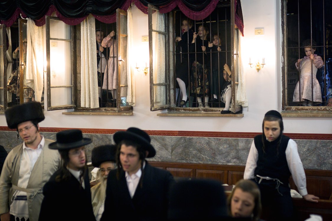 Young Ultra Orthodox girls watching the Simhat Torah celebrations from outside of windows in Jerusalem's Mea Shearim neighbourhood on October 24, 2016. Jews marking the end of the annual cycle of the reading of the Torah and the beginning of the next cycle. In Judaism, especially in Orthodox tradition, there are a number of settings in which men and women are kept separate in order to conform with various elements of halakha and to prevent men and women from mingling. Other forms of Judaism rarely separate genders any more than secular western society. While Jewish modesty law requires gender separation under various circumstances, observers have contended that there is a growing trend among some groups of Hasidic Haredi Jews to extend its observance to the public arena. In Israel, residents of Meah Shearim were banned from erecting a street barrier dividing men and women during the nightly week-long Sukkot festivities and street signs requesting that women avoid certain pavements in Beit Shemesh have been repeatedly removed by the municipality. Photo by Sebi Berens.