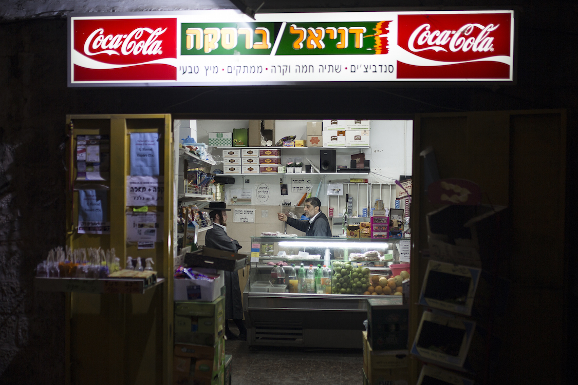 Two Ultra Orthodox Haredim seen chatting in a small supermarket in the Ultra Orthodox neighbourhood of Meah Shearim, Jerusalem on Januar 9th, 2016. The Haredim are relatively materially poor, compared to other Israelis, but represent an important market sector due to their bloc purchasing habits. For this reason, some companies and organizations in Israel refrain from including women or other images deemed immodest in their advertisements to avoid Haredi consumer boycotts. Photo by Sebi Berens.