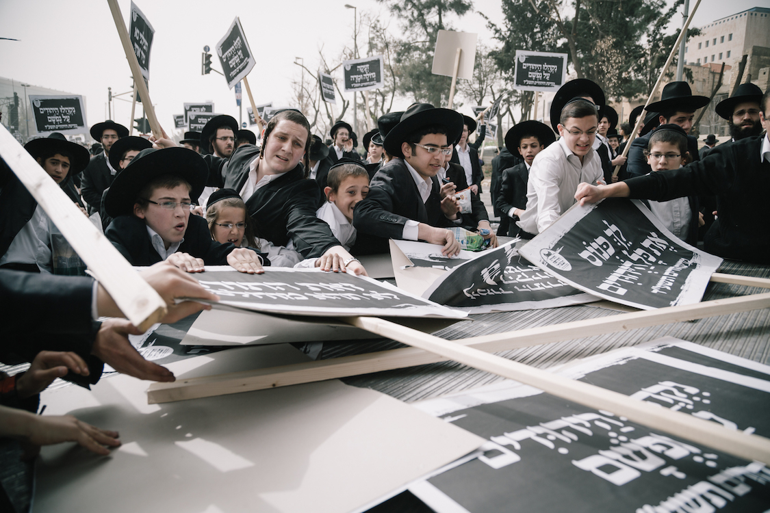 Young Ultra-Orthodox Haredim try to catch demonstration signs on a protest in Jerusalem on 2th March, 2017, at a bill that would cut their community's military exemptions and end a tradition upheld since Israel's foundation. Ultra-Orthodox leaders had called on their men, women and children to attend the protest against new legislation ending the wholesale army exemptions granted to seminary students. Police said hundreds of thousands took part in the prayer. Israeli media estimated that between 250,000 to 400,000 attended. Photo by Sebi Berens