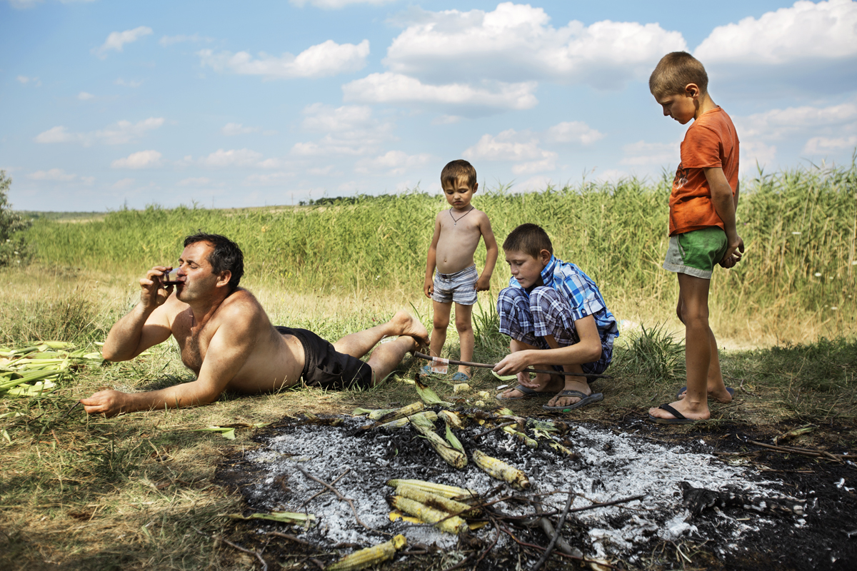 Moldova. Beshalma, Gagauzia - July 2017  Vadim while dries up banknotes after a bath at the lake. On holiday days, men and kids often go to the field to play and spend moments of relax.