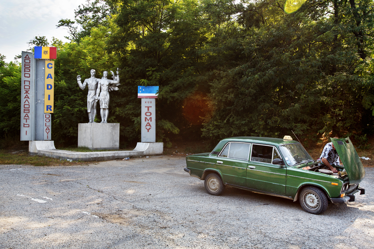 Moldova. Tomay, Gagauzia - July 2017  Taxi driver stoped to check his car along the road Comrat-Ceadir Lunga. In the background the welcome Monument in the region of Ceadir Lunga, at the entrance of the city of Tomay.