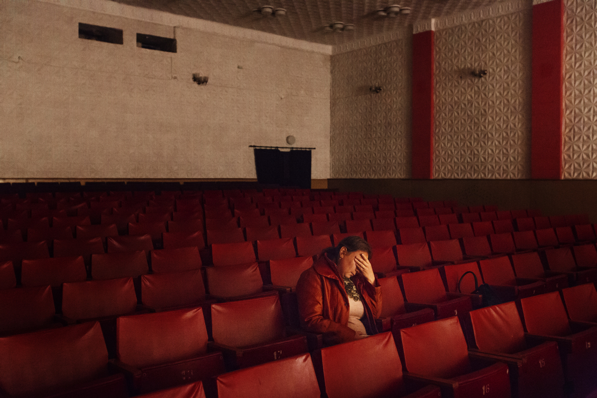 Moldova. Comrat, Gagauzia - November 2017A tired woman sitting in the cinema of the House of Culture in Comrat, the capital of Gagauzia, while memebers of the staff are setting the projection of the first Gagauz movie in Gagauz language.