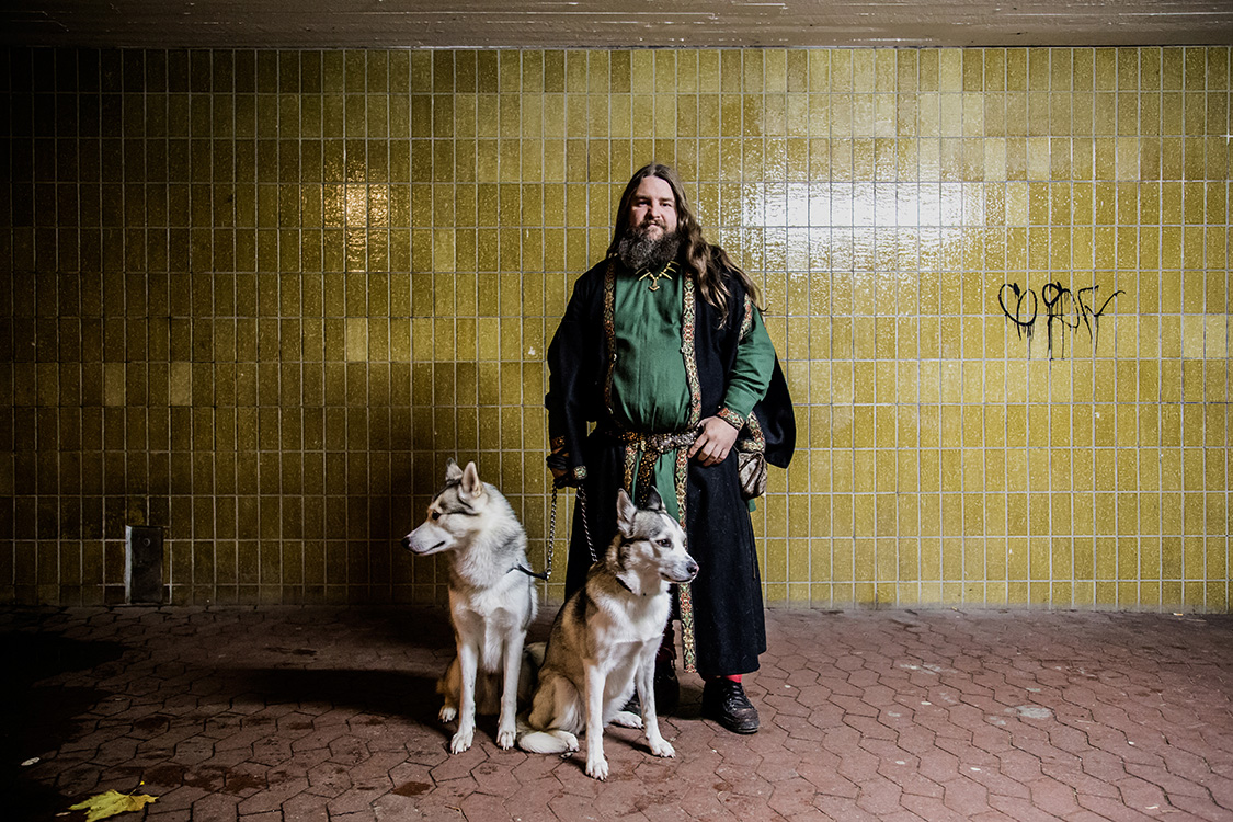 Carl Mikael, an history expert and viking priest, poses for a portrait with his dogs, in a subway in Malmo, Sweden.
