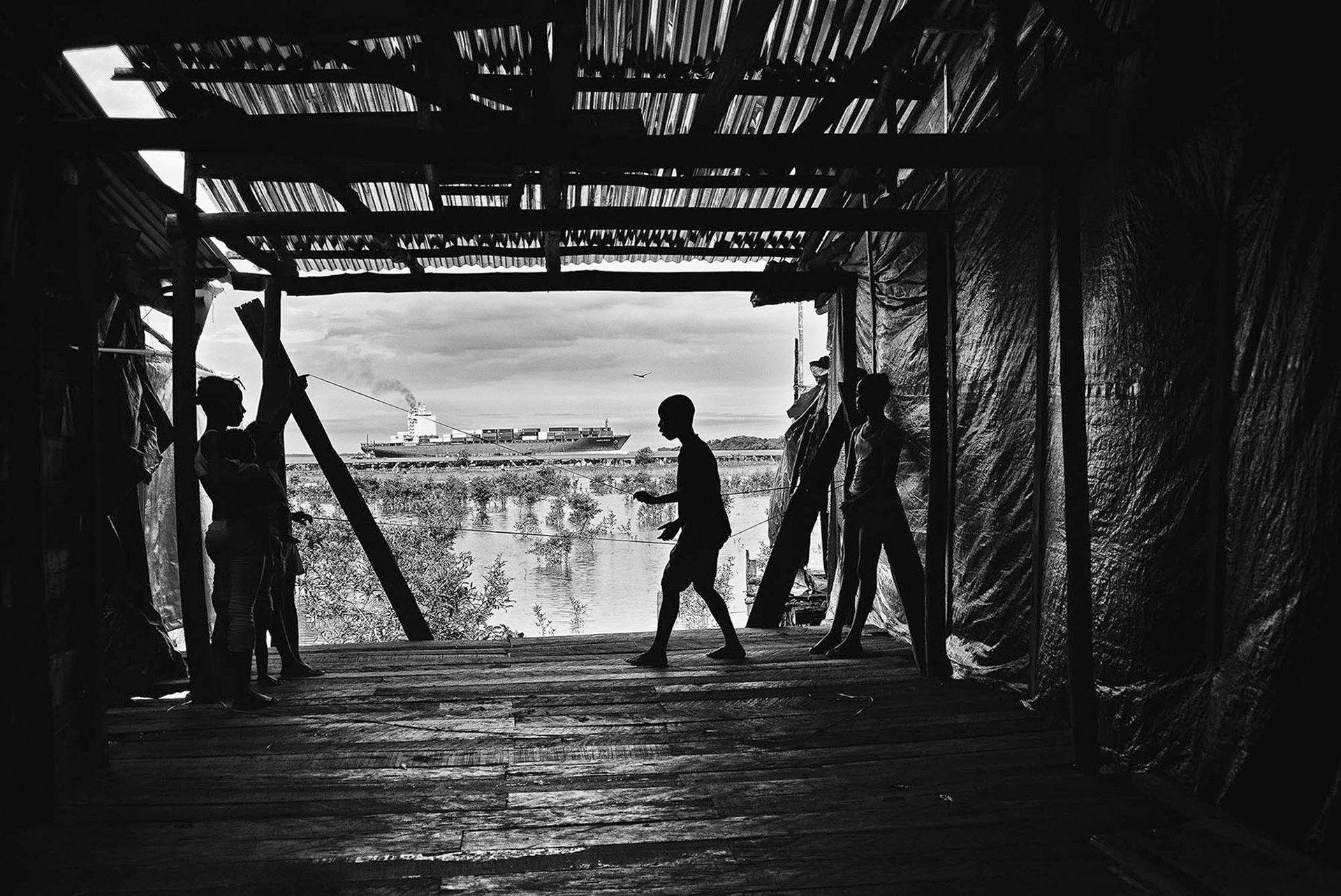 kids play in a shack in the SAn José barrio in front of a cargo coming in the port of Buenaventura.