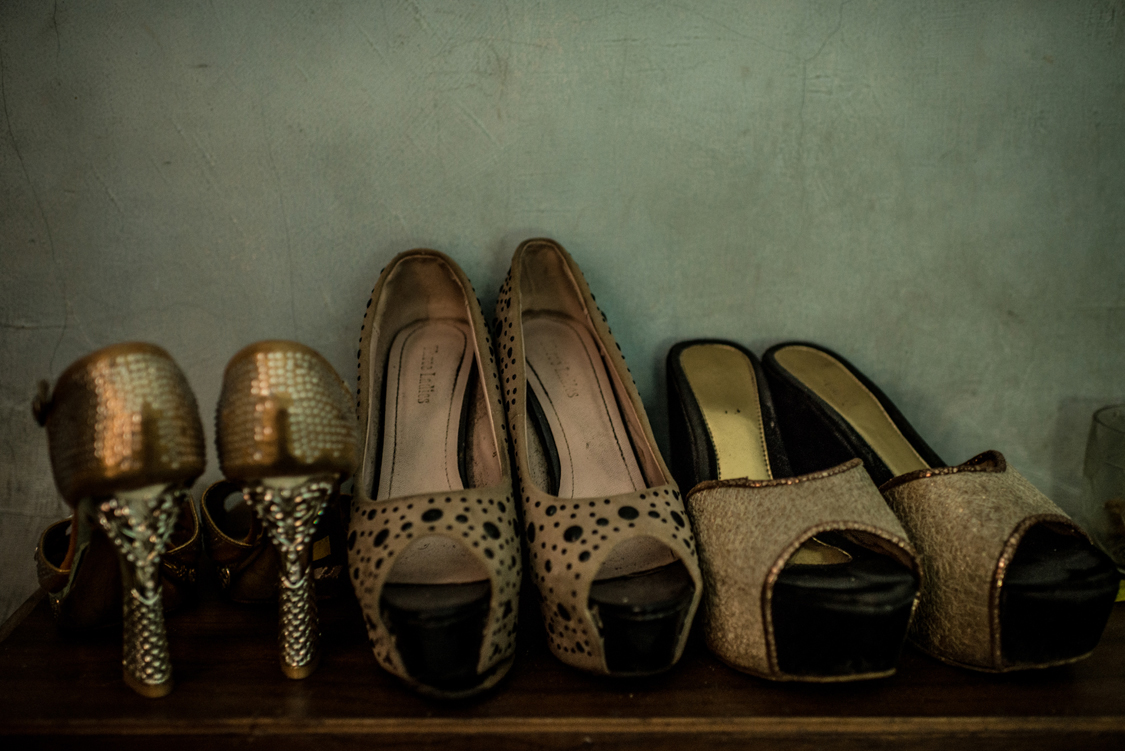 The golden high heels shoes of a young waria, street sex worker, are well sorted on the shelf in her tiny rental room. Jakarta, Indonesia, 23rd February 2017