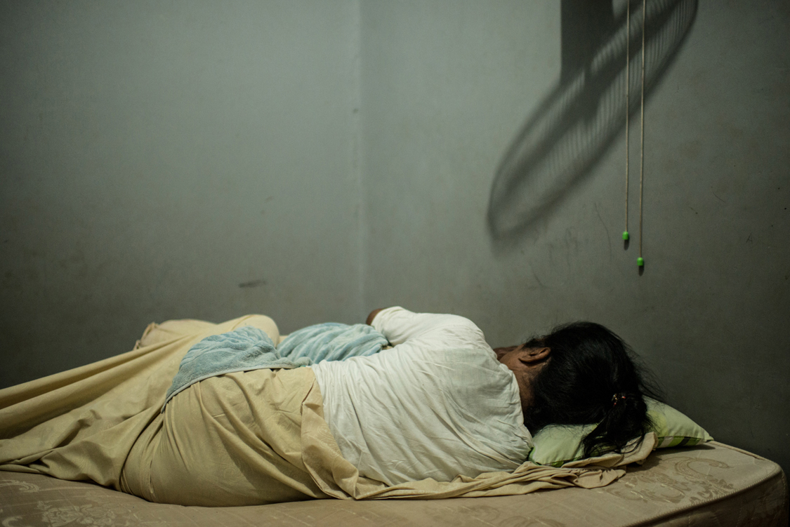 """Mami Yuli, aka Yulianus Rettoblaut, born 1961, sleeps in her room in the shelter house for elderly waria. She is the leader of Indonesian waria, an """"umbrella"""" word, that stands for transgender and transvestite people.  Jakarta, Indonesia, 8th June 2014."""