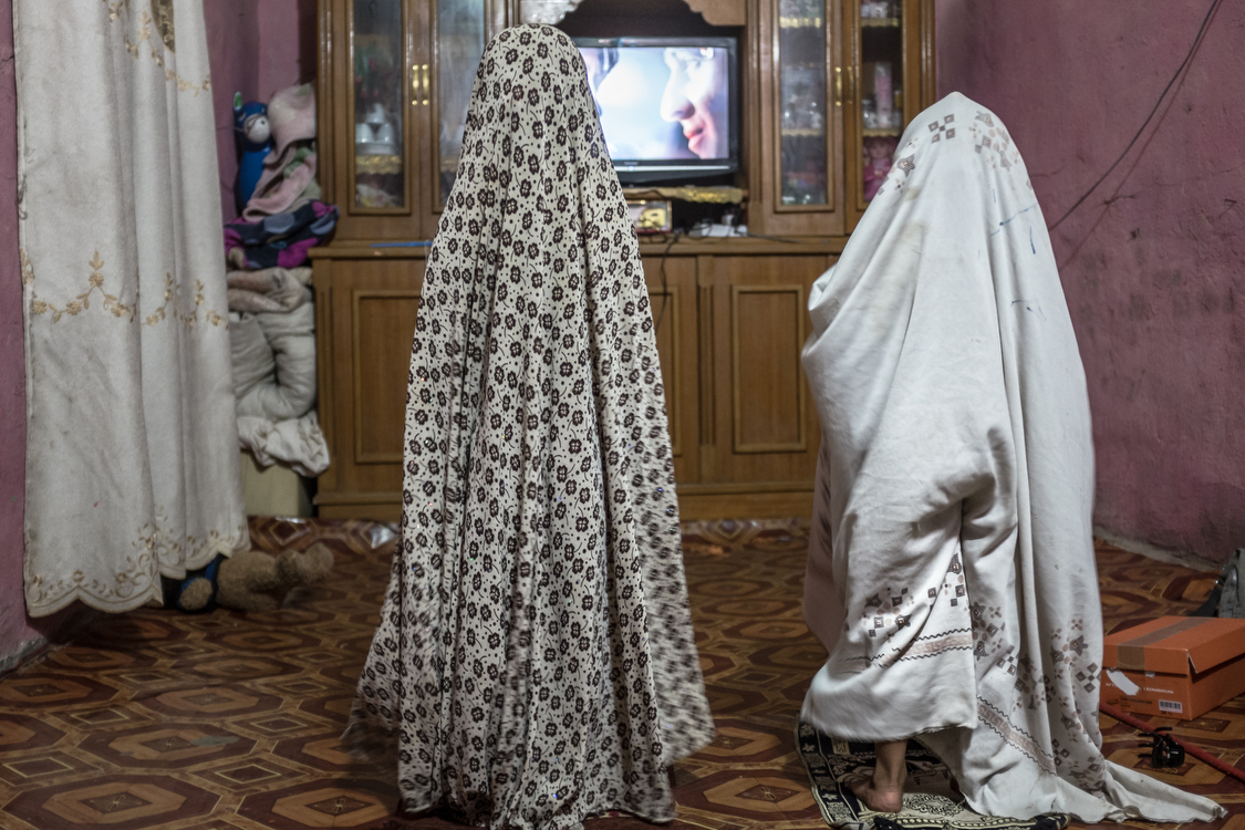 Fatma (left) and Tiktum play as if they were praying, in their house in Chibayish, Southern Iraq. Iraq, 23/08/2017