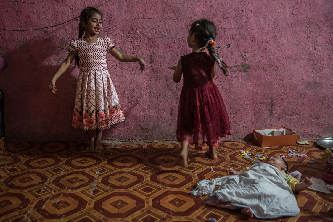 Fatma and Tiktum dance at home on a birthday while their newborn brother, Abdallah, is laying on the floor.Iraq, 04/10/2018