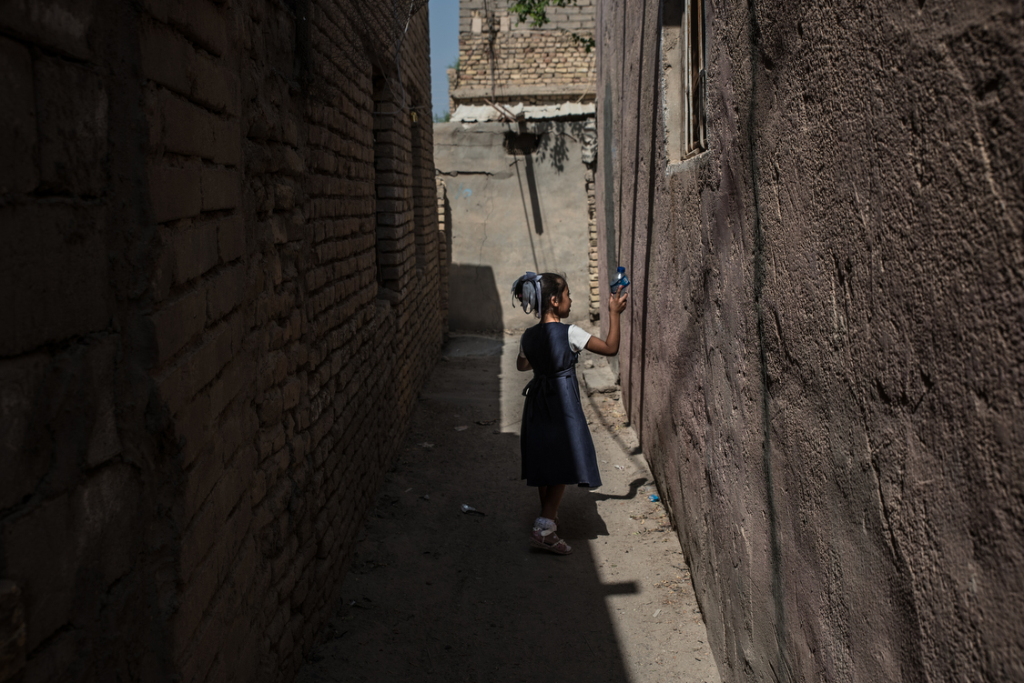 Fatma comes back home from school at noon. Unlike some other little girls in Chibayish, her parents let her go outside without covering her hair, arms or legs. Iraq, 11/10/2018