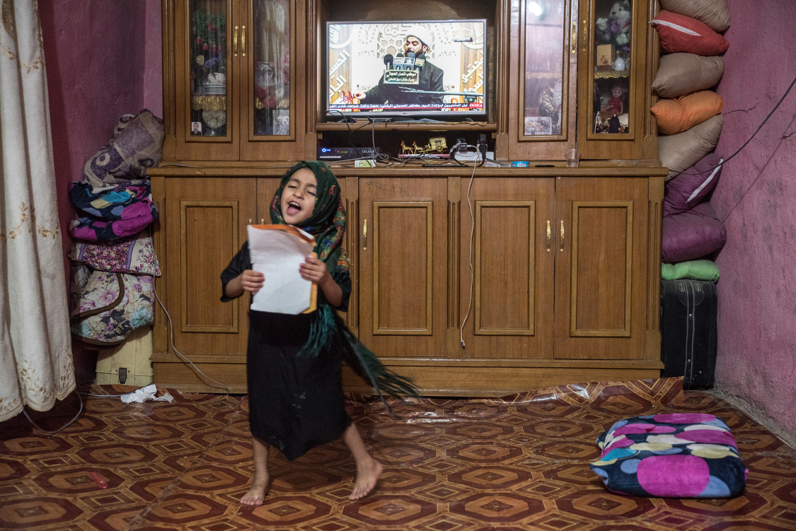 Tiktum, 6, dances and chants as a Shiite cleric is talking on TV. She sings a mix of names, random words, and bits of the Fatiha, the first Sura from the Qur�an that she is currently learning at school. Iraq, 04/10/2018