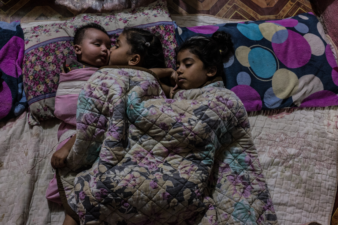 Fatma, Tiktum and Abdallah lay in bed just before going to sleep. The whole family sleeps on a blanket on the floor, in the main room of the house. Iraq, 15/10/2018