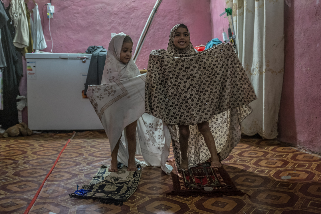 """Fatma and Tiktum """"fake"""" a prayer. They have costume """"abayas"""" that they use for playing. Iraq, 23/08/2017"""