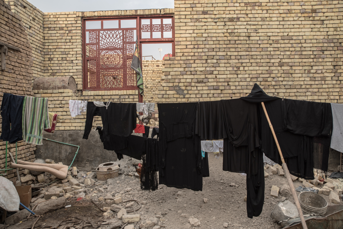 Black clothes hang in front of the family's house. During the month of Muharram, which symbolizes the mourning of Imam Hussein's death, Shiite muslims only wear black. In very conservative Chibayish, women wear black abayas all year round. Iraq, 16/10/2018