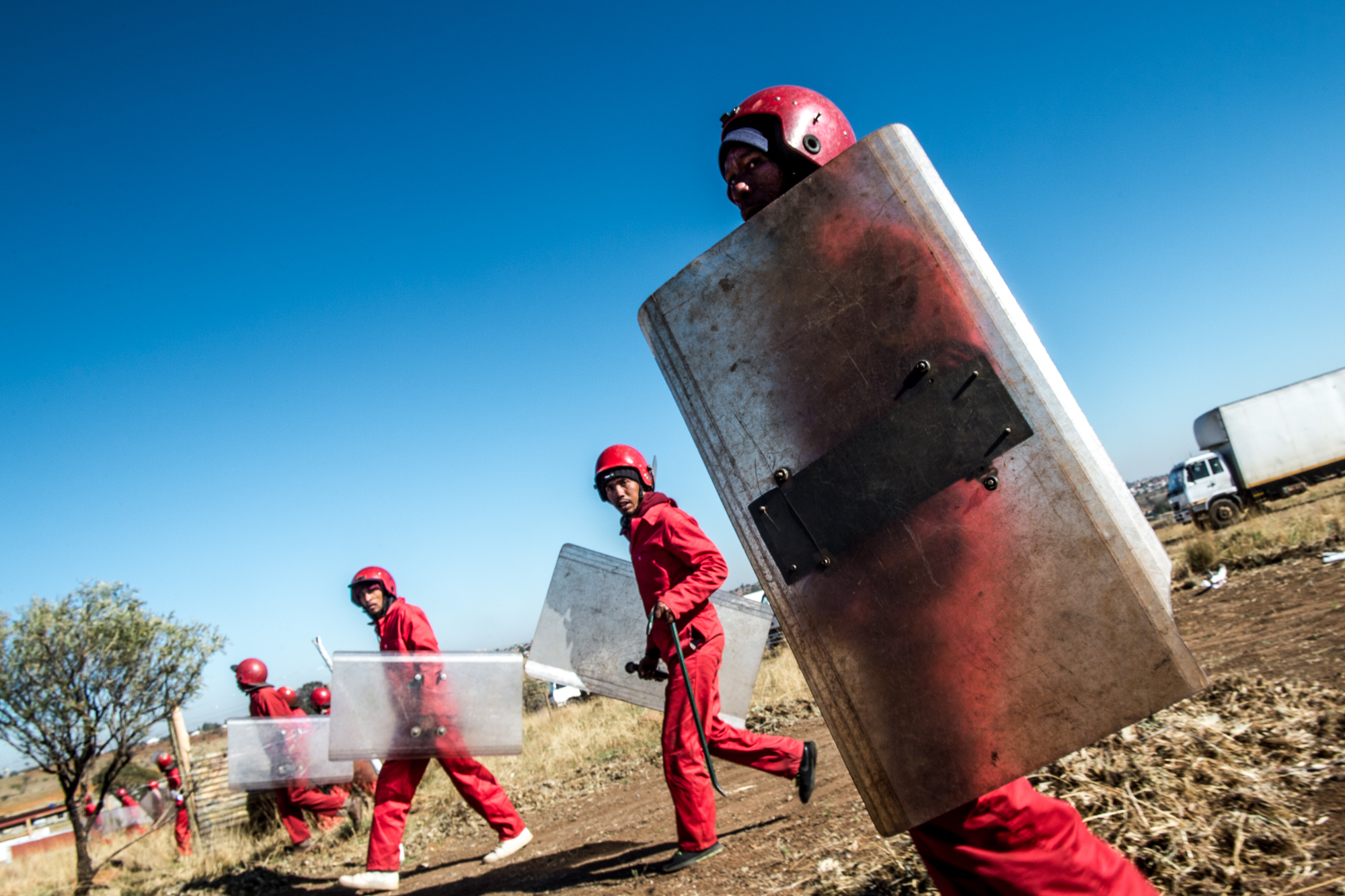 South Africa, Soshanguve, 11.09.2018 // Landgrabbs are occurring more often lately. In this instant, like in many others, the police refused to clear the settlement, so the Red Ants eviction-service was called in to storm the settlement with shields and crowbars. // Lucas Bäuml