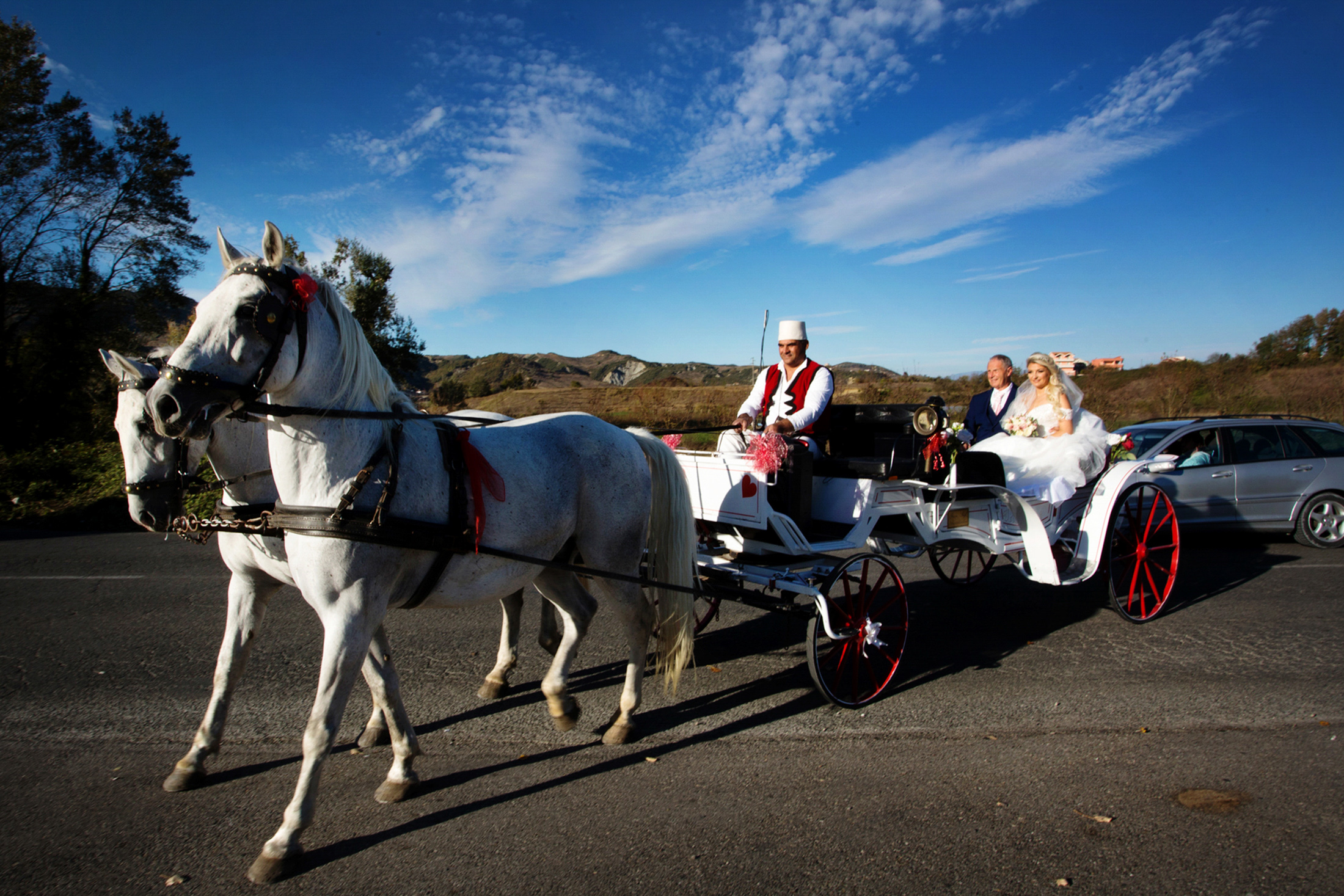 A horse drawn carriage is driving a bride and her father to the wedding venue outside of Tirana, Albania.