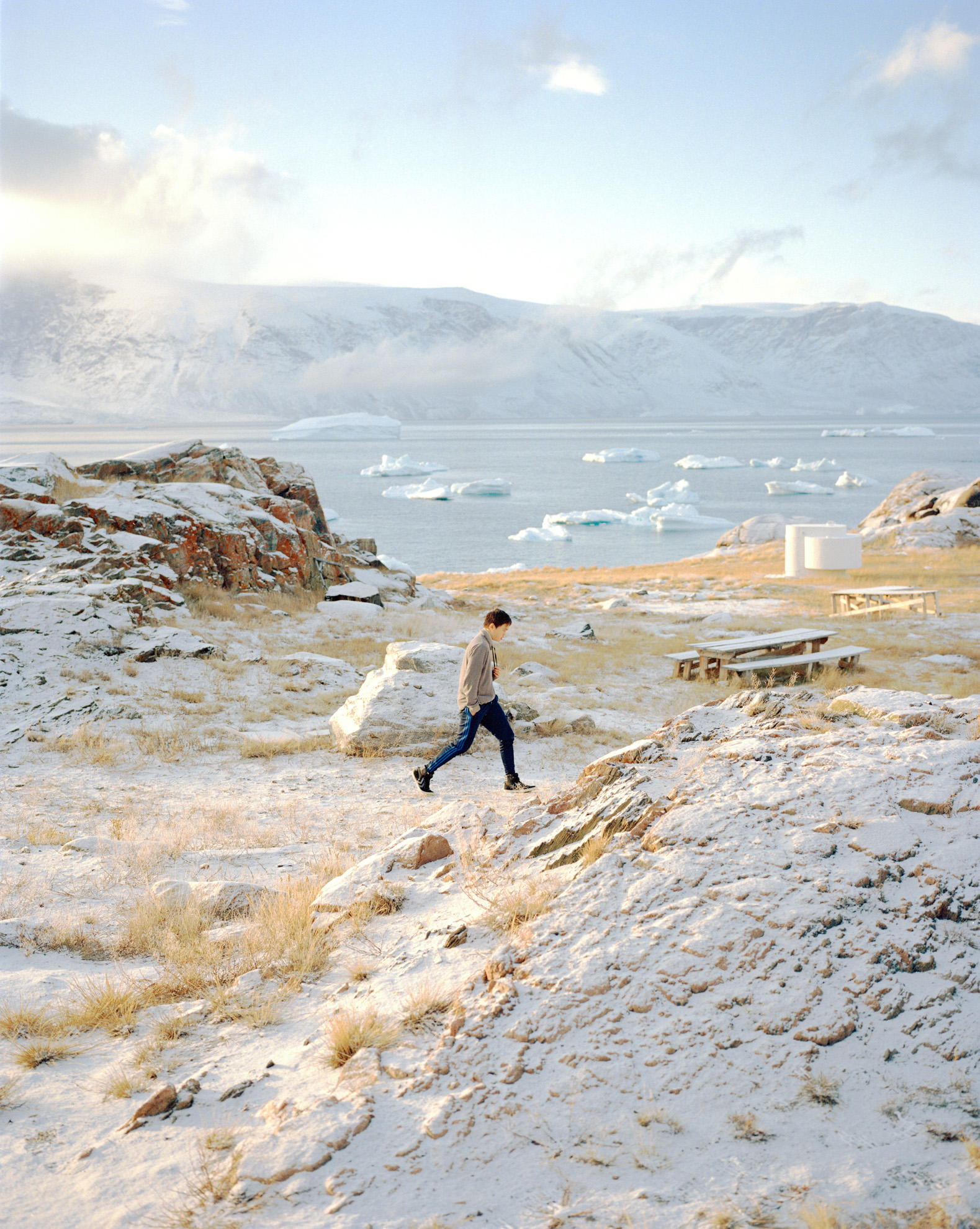 A young boy is walking through a winter landscape in one of the abandoned settlements around Uummannaq which is now used by the Uummannaq children's home to get kids away from daily routines or bad habits like smoking for some weeks. Greenland's remote landscape can be stunning and beautiful.