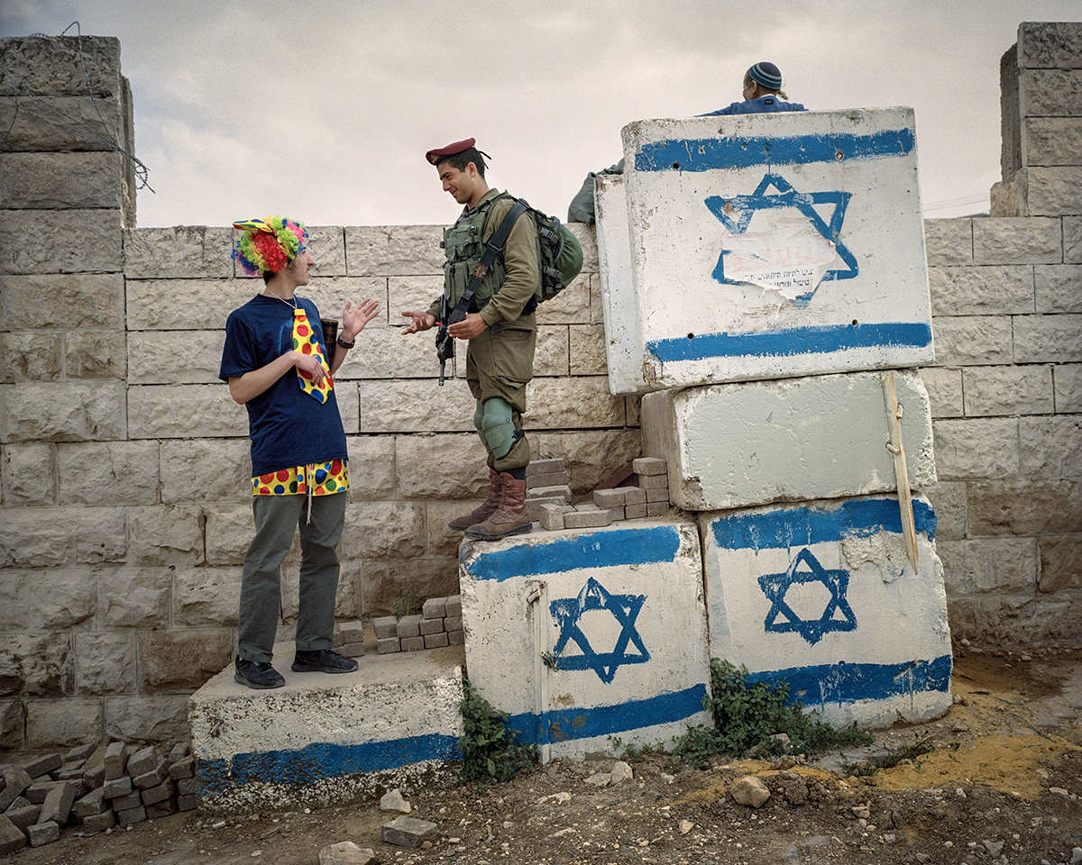 12. Maerz 2017. Hebron, Westjordanland. Ein israelischer Soldat scherzt mit einem Siedler herum, der sich fuer das Purimfest verkleidet hat. Purim ist ein froehliches Fest, die Menschen kostuemieren sich, und der Alkohol fliesst. Gefeiert wird die Rettung der persischen Juden in biblischer Zeit: Koenigin Ester bewahrte damals das juedische Volk im Persischen Reich vor der Vernichtung. In der Altstadt und damit mitten unter der palaestinensischen Bevoelkerung von Hebron leben rund 800 religioese Siedler. Militaerische Infrastruktur wie Mauern, Checkpoints sowie permanente Praesenz der Armee sorgen fuer die Sicherheit der Siedler.
