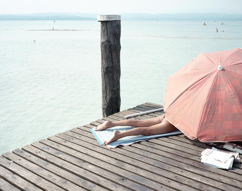 Sirmione, 2017, ItalyA woman getting sun bath on the pier of Lake Garda in Sirmione