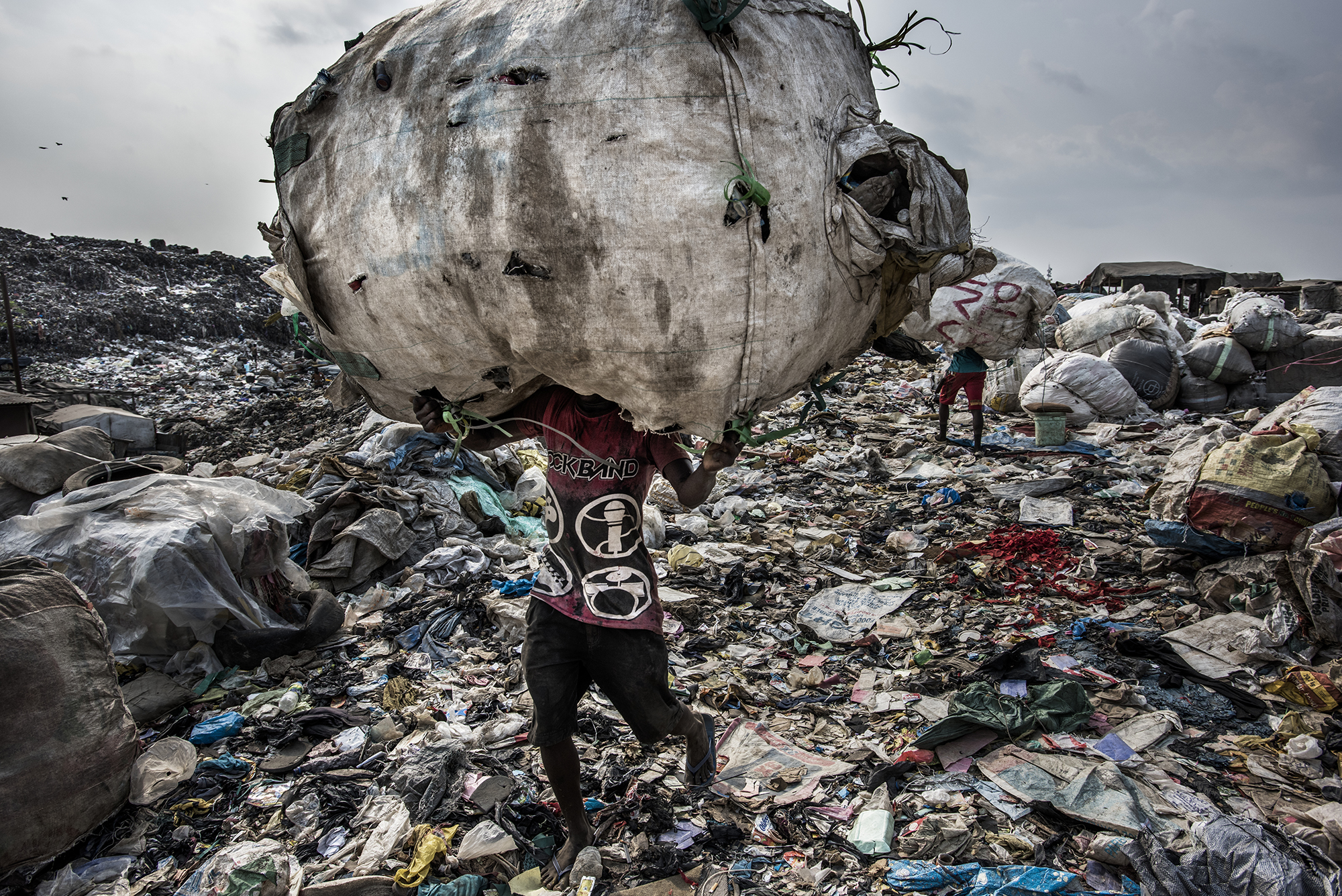 Nigeria, Lagos, 27 January 2017A man carries a huge back of pet bottles collected for recycling at the Olusosun landfill.The Olusosun landfill in Lagos receives between 3-5000 tons per day and is about 45 ha in size. About 5000 scavengers work here and often also live. They collect anything that is recyable like plastics, textiles, electronics, paper etc. The problem is that the landfill is full and the city wants to close it down. The question is where it will go, there are no incinerators and the infrastructure to formally recycle is lacking. There is one other landfill, but it needs to close as well.Remarkable is that the landfills in Lagos smell less compared to other landfills in the world: Nigerians throw away less food, because they either finish their plate or feed it to the animals.Kadir van Lohuizen / NOOR