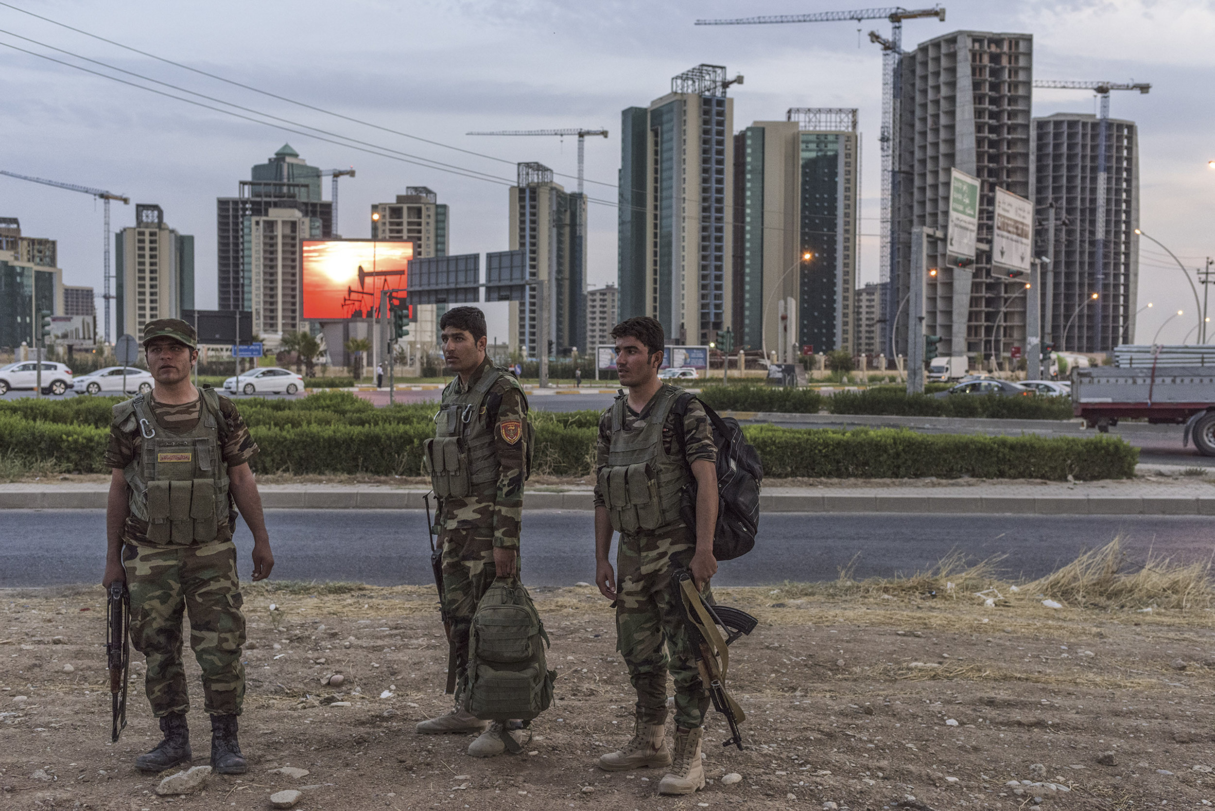 """Iraqi Kurdistan, Erbil, September 2015, Peshmerga returning from the front line wait for a lift on the outskirts of Erbil. Behind them looms a skyline of unfinished buildings, a reminder of a more hopeful era. """"We haven't been paid in months,"""" says one soldier. """"It doesn't matter. We would all die for Kurdistan."""""""