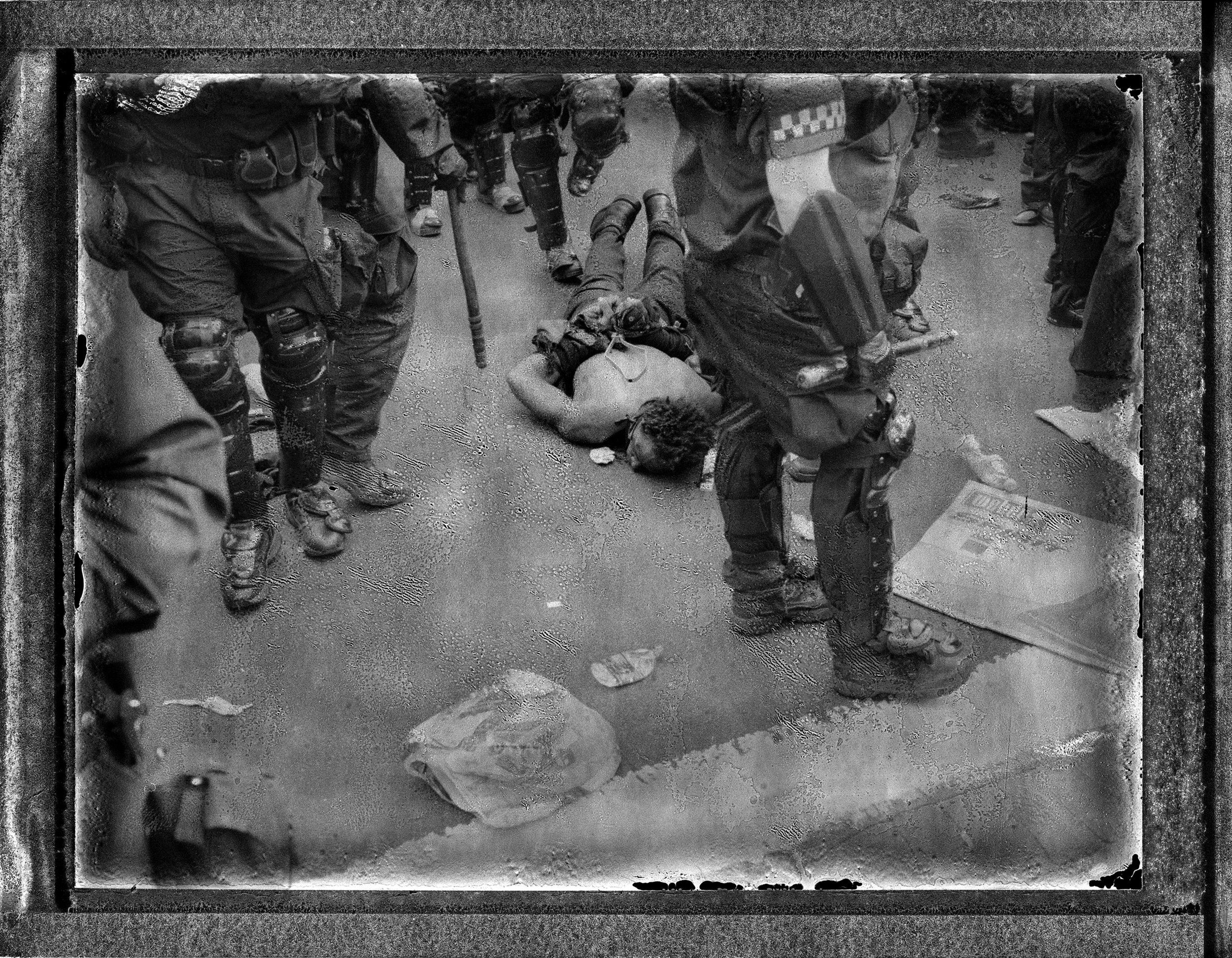 USA, Chicago, May 2012, A protester who was beaten and arrested by the polices lies bloodied on the pavement of Cermak Road on Chicago's South Side after protesting the NATO Summit.
