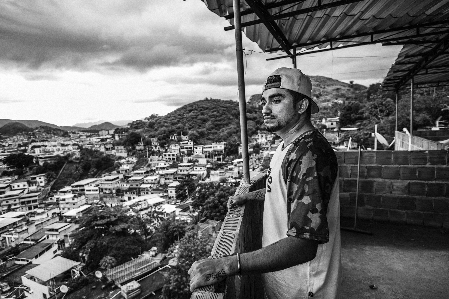 February 2015 - Rio de Janeiro, Brazil: Raul, one of the members of Papo Reto collective, with a general view of the Complexo do Alemao.