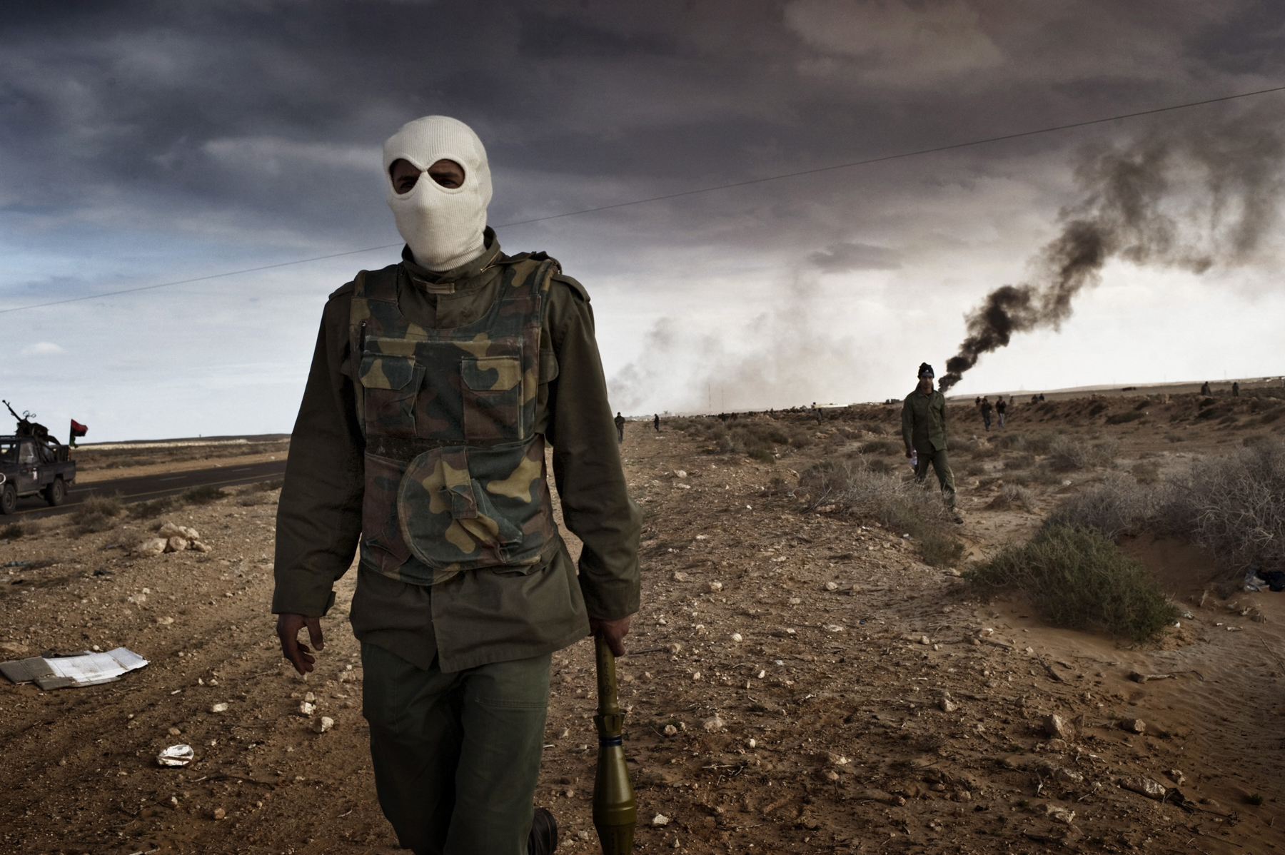 RAS LANUF, LIBYA - MARCH 09: Libyan rebels advance during a battle with government troops as an oil facility burns
