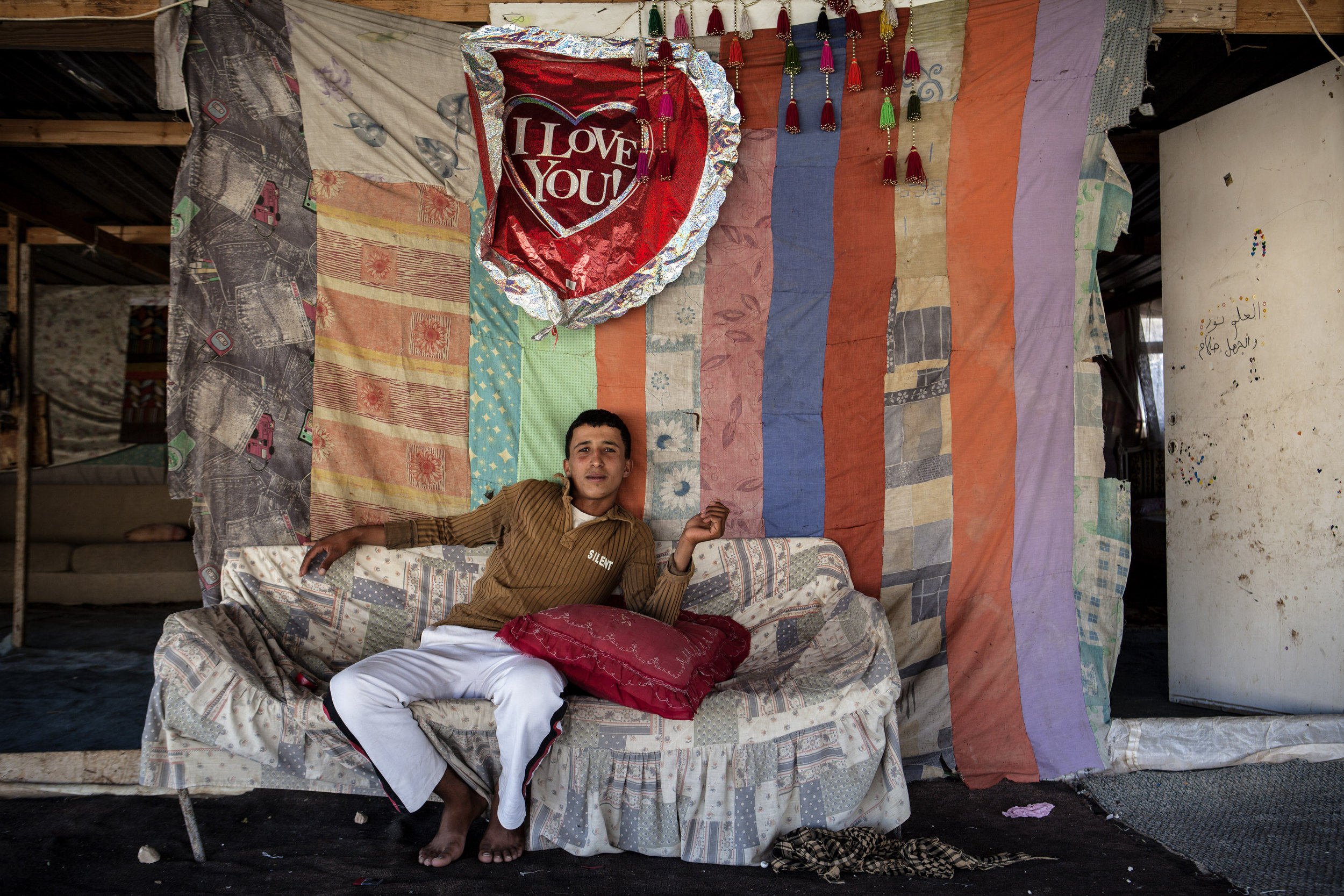 Occupied Palestinian Territories, Khan al-Ahmar, 03 July 2012  Young man from Khan Ahmar relaxes in his home.  A graduate of the only school present in area for the Bedouin, his future plans include working illegally as a builder for various Israeli construction projects.  Tanya Habjouqa / NOOR