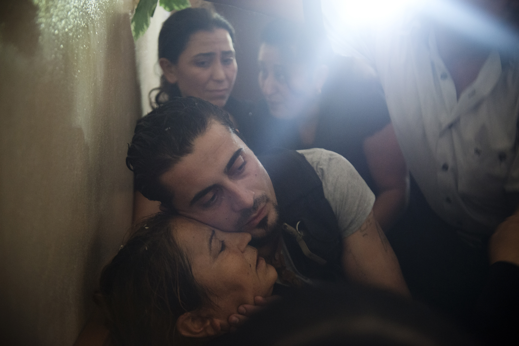 Bassel Barhoum hugs his mother Jamila Marshid during his brother's funeral in the village of Daqaqa in Latakia Province, Syria. Abu Layth died while fighting for the Syrian Army. 