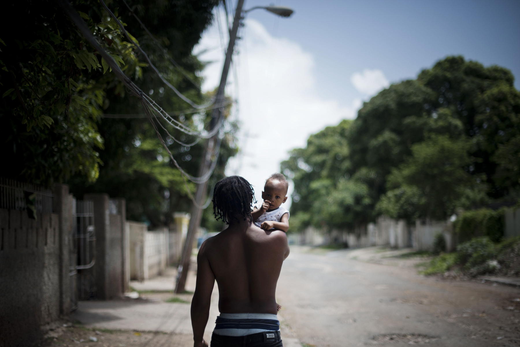 A man walks with his child on the streets of Mountain View in Kingston, Jamaica. 