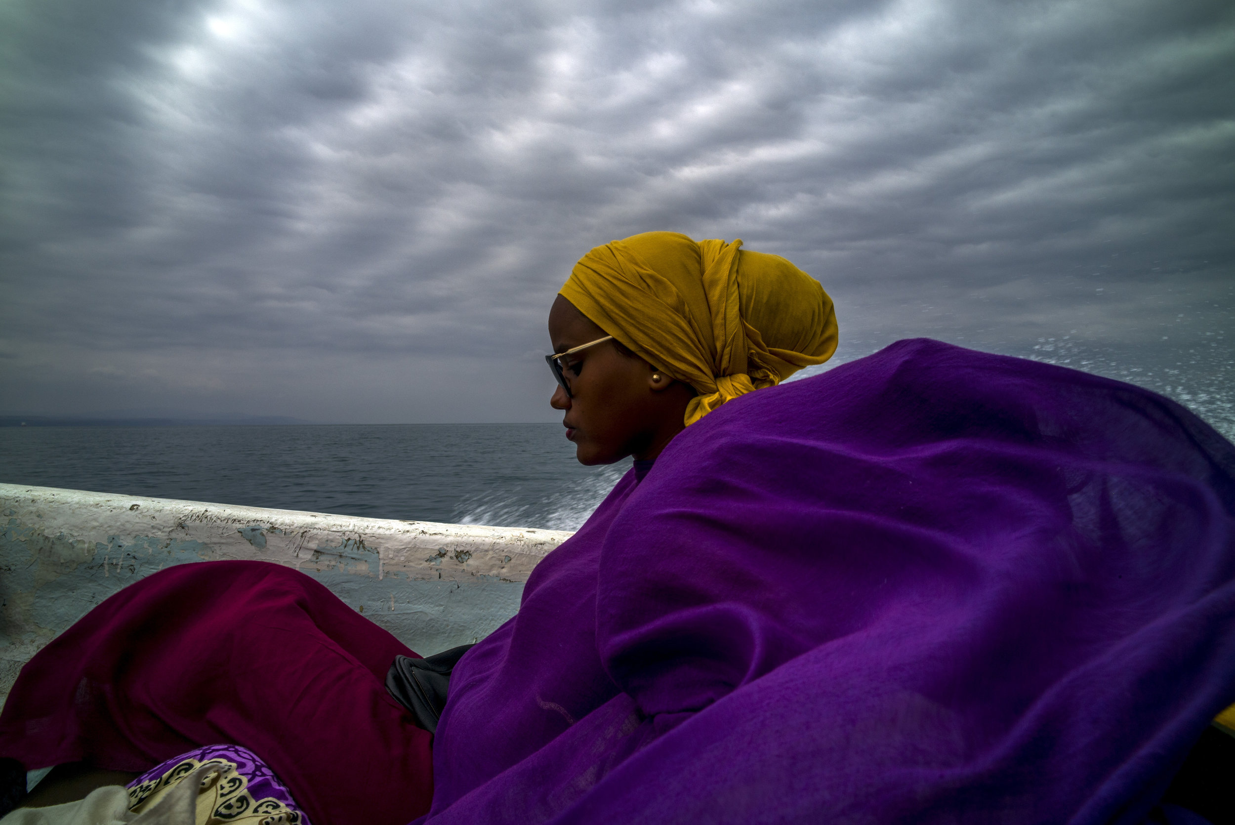 OBOCK, DJIBOUTI - DECEMBER 2018  Crossing the sea from Obock, two women in wrapped in colourful scarves travel in a small, fibreglass speedboat used to transport the narcotic khat. Chewed on a daily basis by much of the male population surrounding the Gulf of Aden?s shores, trade in the lucrative khat business often goes hand in hand with other forms of smuggling.
