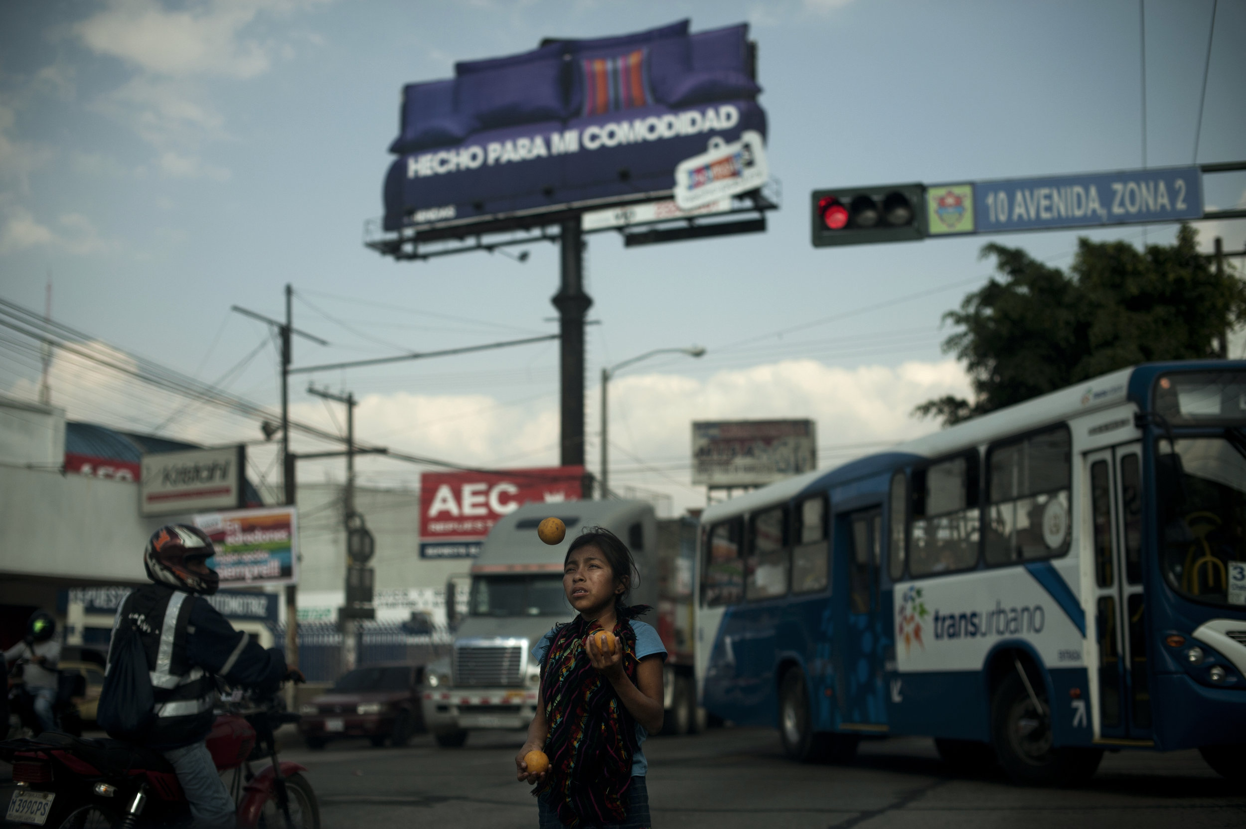 A young girl juggles oranges for money at a stoplight in Guatemala City traffic. 