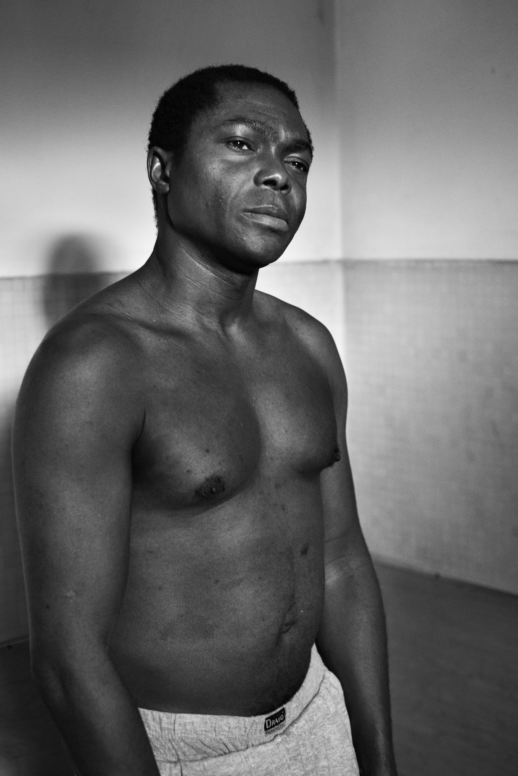 Rok Ibe (30) in the showers� entrance inside the Public Baths of Via Bianz� in Turin, Italy; December 2018.Mr. Ibe lives with his parents on the outskirt of Torino; given that they can�t afford to pay housing bills, they are forced to live without heating and hot water.