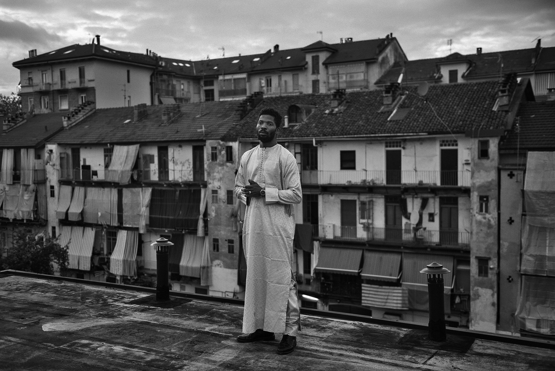 Jacob Bamba (30) portrayed in the rooftop of the Public Baths of Via Agliè in the working-class district of Barriera di Milano in Turin, Italy; November 2018.Mr. Bamba - who arrived in Turin when he was 18 - has lived for 2 years in a small apartment with 12 people; frequenting the public showers' social network had allowed Mr. Bamba to free himself of a degrading condition. He now works as cultural mediator and is well-known in the troubled neighbourhood as a social rapper, advocating for migrants' integration and better life conditions.