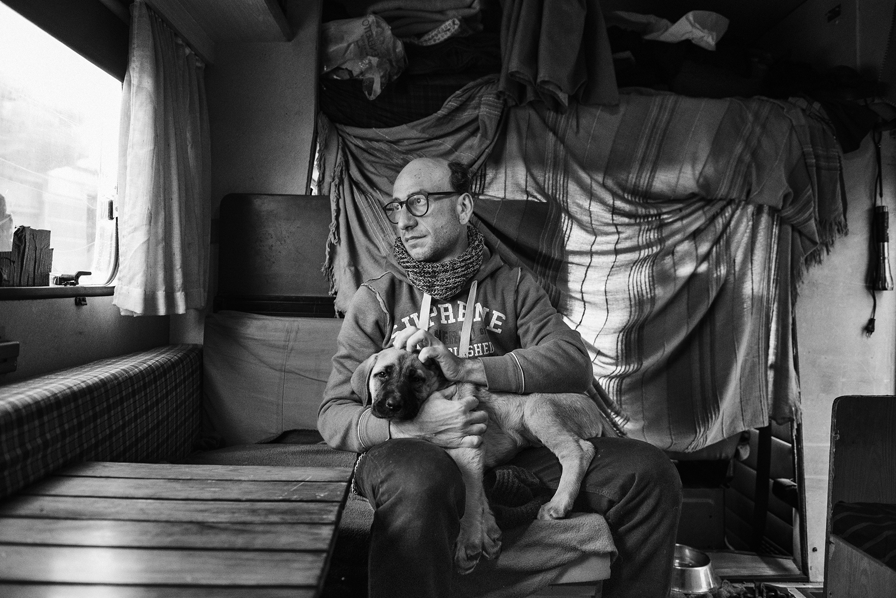 Marcello Fonti (43) look out of the window of the RV he lives in, parked outside the Public Baths of Via Agli� in the working-class district of Barriera di Milano in Turin, Italy; November 2018.Mr. Fonti has not a home since 2003, moving around Torino from place to place in his old RV; during the summer he bath himself open air, in rivers and streams, but in the cold months he goes to the Public Baths for a hot shower.