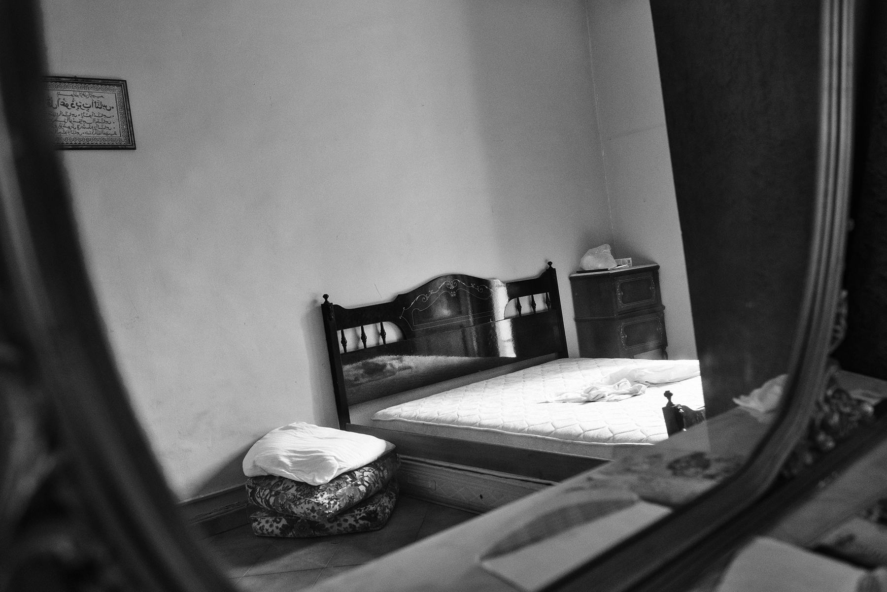 The sleeping room of an apartment inhabited by a family of four, with a shared toilet on the balcony, in the working class district of Barriera di Milano in Turin; July 2017.
