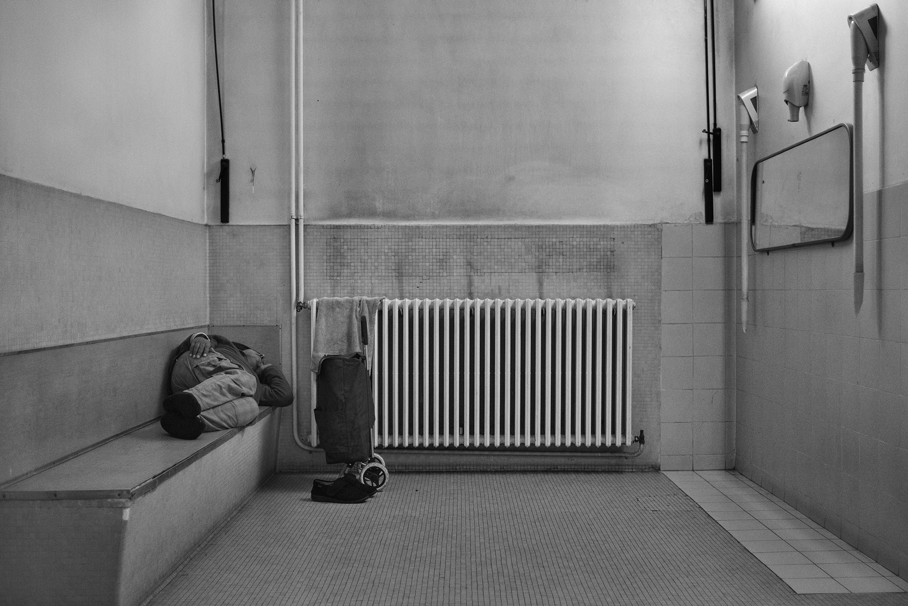 A man sleeps inside the Public Baths of via Bianzé in Turin, Italy; December 2018.In the winter season, public shower's users - especially whose homeless - take advantage of the warm environment to rest for a couple of hours, even if it is theoretically forbidden.