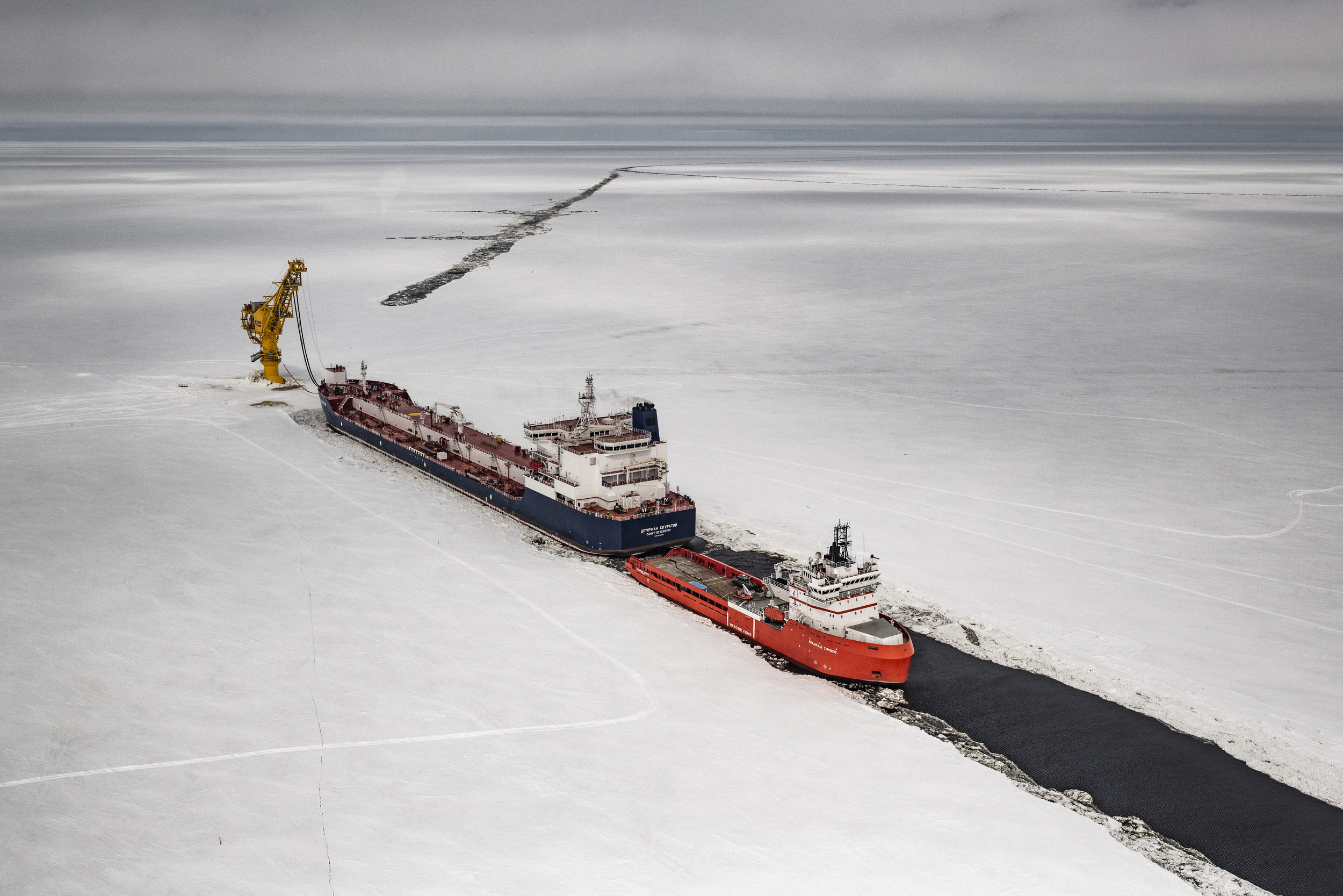 """Russia, Yamal Peninsula, Cape Kemenny, May 2018Gazprom Neft's """"Arctic Gate"""" terminal in Gulf of Ob  The Novoportovskoye is one of the biggest oil fields in the Yamal Peninsula. The field is located 30 km from the coast of the Ob bay, and oil is transported by pipeline to Cape Kamenny where a terminal facility has been developed. The company Gazprom Neft is operating the Novy Port project, which is built to be able to deliver up to eight million tons of oil per year.  A fleet of six tankers are being built for the Novy Port. The first vessels of the new fleet, the �Shturman Albanov� and the �Shturman Malygin� were put on the water in early 2016. The third fleet tanker, the ?Shturman Ovtsyn? set course for the history books when it in mid-winter 2017 left the yard of the Samsung Heavy Industries in South Korea, made it through the Bering Strait and sailed all the way to Yamal. Later, also the �Shturman Shcherbinin� and the �Shturman Koshelev� were built.Yuri Kozyrev / NOOR for Carmignac Foundation"""