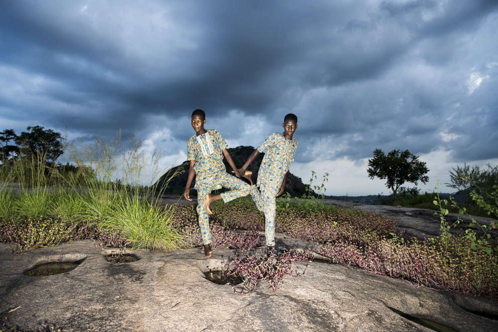 NIGERIA, Igbo-Ora, October 2018.In this picture identical twin brothers are copy eachothers body language by a pond on a mountain close to their village in front of a rainy season sky about to burst out in a lightning storm.Igbo-Ora, the self proclaimed 'Twin Capital of the World' has earned its nickname by the unusually large number of twin births in the region. Research has suggested that the multiple births could be related to the (over)consumption of local crops by the women in the region of Igbo Ora. Although no direct relation between dietary intake and twin births has been proved, a research study carried out by the University of Lagos Teaching Hospital has suggested that a chemical found in Igbo-Ora women and the peelings of a widely consumed tuber (yams) could be causing twins births. Another possible explanation is genetics.