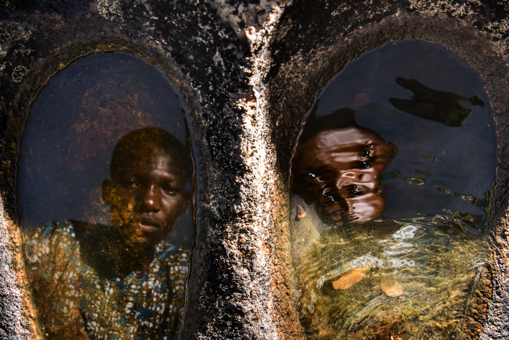 NIGERIA, Igbo-Ora, October 2018.Showing us around on a rock with little natural pools -close to their village- these identical twin brothers were looking in the water, one of them moving the water with his hand (cropped out of the image) the reflection of his face being distorted by the movement of the water.Igbo-Ora, the self proclaimed 'Twin Capital of the World' has earned its nickname by the unusually large number of twin births in the region. Research has suggested that the multiple births could be related to the (over)consumption of local crops by the women in the region of Igbo Ora. Although no direct relation between dietary intake and twin births has been proved, a research study carried out by the University of Lagos Teaching Hospital has suggested that a chemical found in Igbo-Ora women and the peelings of a widely consumed tuber (yams) could be causing twins births. Another possible explanation is genetics.