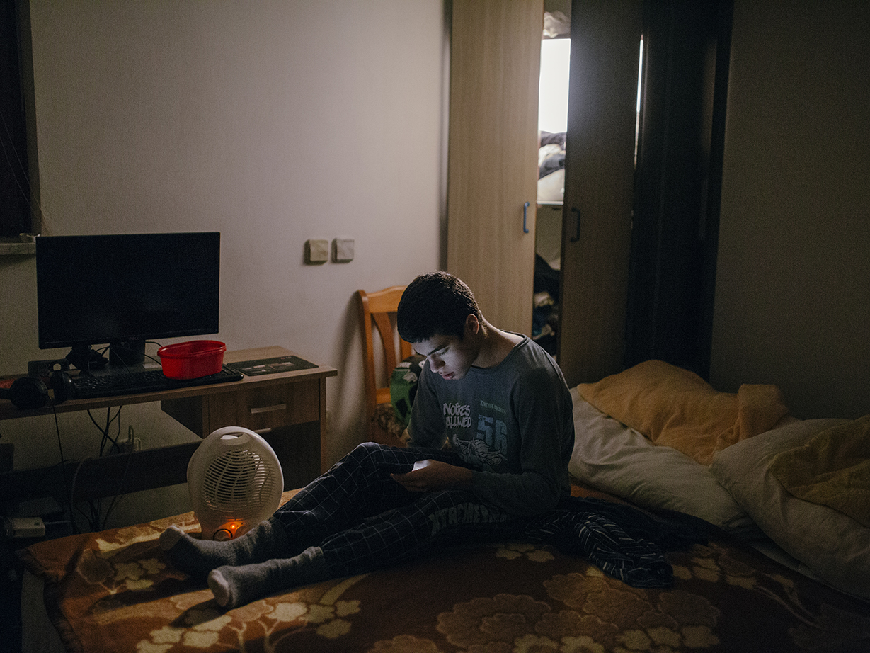 The conditions in the apartment where Nikola and Nenad live are not very good, it is very cold in the room where they sleep and spend their time. Nikola tries to warm up before going to school. Kranj, Slovenia/2019Photo/Vladimir Zivojinovic