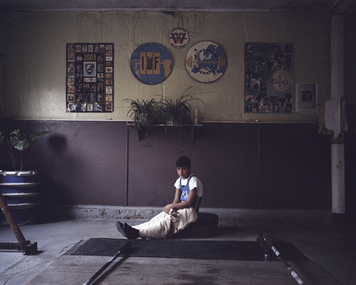A boy is warming up his leg muscles after his round on a regional weightlifting championship.