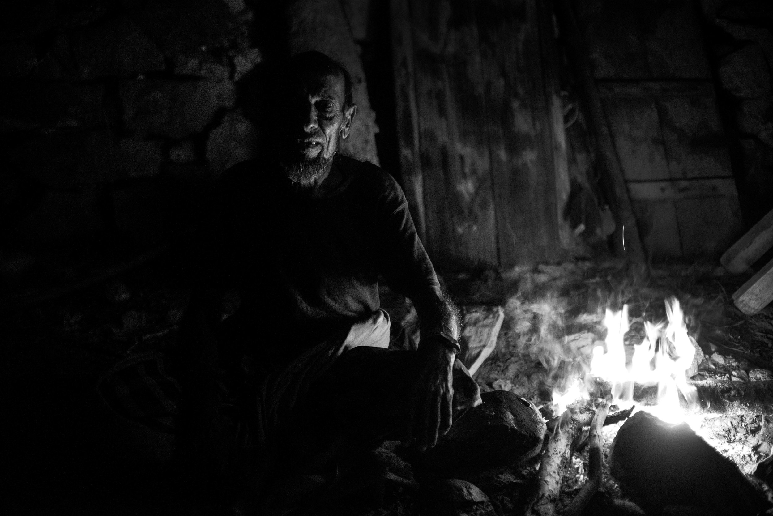 Project Socotra: The invisible Island February 2019 Old Bedouin pose for a picture next to the fire in his house in the Dragon Blood Tree forest. Many people migrate towards the city and the villages along the coast, some still leave high in the mountain, taking care for their goats and leaving as their ancestors once did.