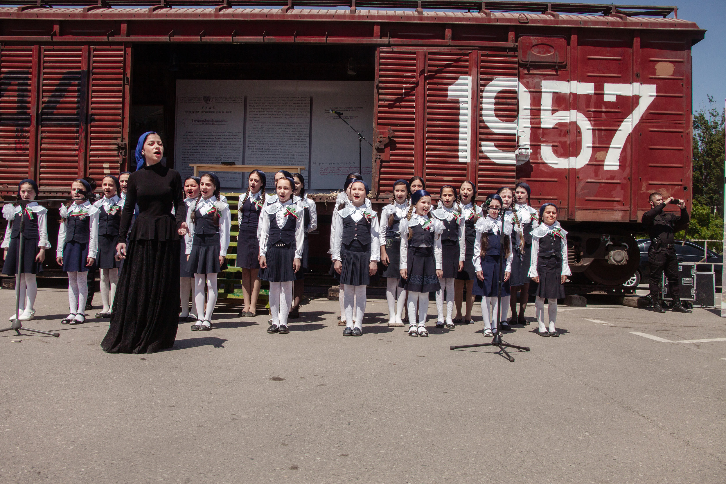 Russia, Chechnya, Grozny, 10 May 2013. A choir of schoolgirls singing a song dedicated to Akhmad Kadyrov, next to a train carriage commemorating Stalin's forced deportation of Chechens to Central Asia in 1944. In 1957 Nikita Khrushchev reversed the process.