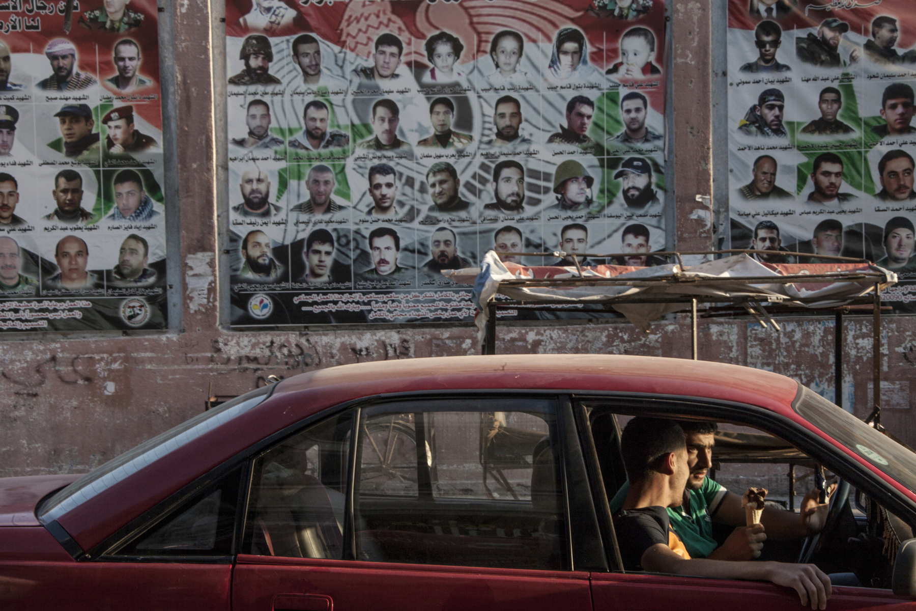 Damascus, 2015, A car with two young men in it is parked next to the so-called Martyrs Garden in the Alawi-dominated neighborhood of al-Zahra in Homs. On the wall behing, thousands of pictures of the Syrian Army soldiers and members of the National Defence who were killed.