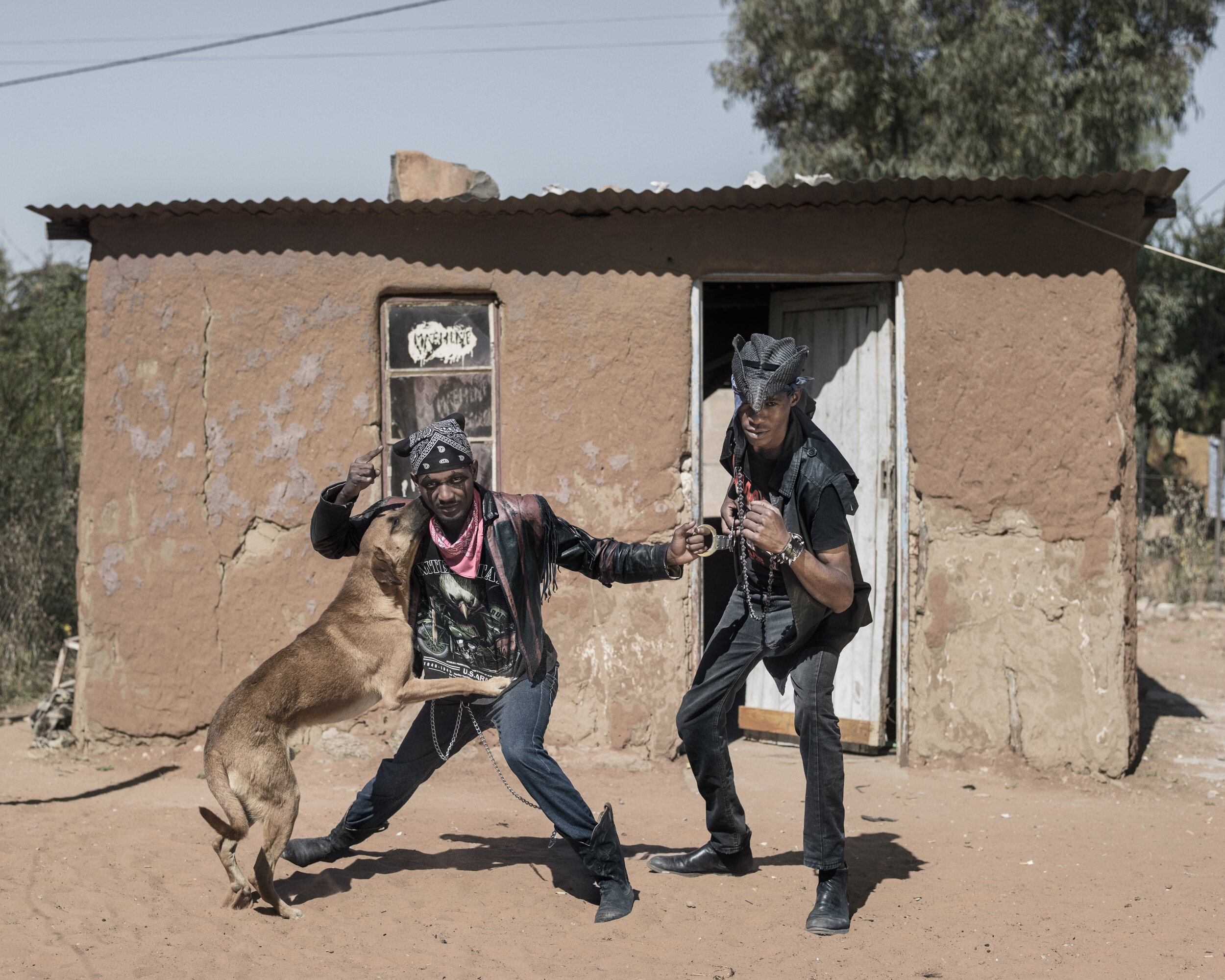 """Botswana, Ghanzi, May 20178th Anniversary Overthrust """"Winter Metal Mania Fest 2017""""  Kehumile Samo (right) and his Cousin Innocent Iane (left) with Lady, the dog. Kehumile studies Public Health in Ghanzi. Innocent wants to become a farmer. They share the house (in the picture behind them, left) on their uncles's property. Their favourites bands are Iron Maiden, Megadeath, Judas Priest but also Meatloaf. They don't have nicknames (yet).Pep Bonet / NOOR"""