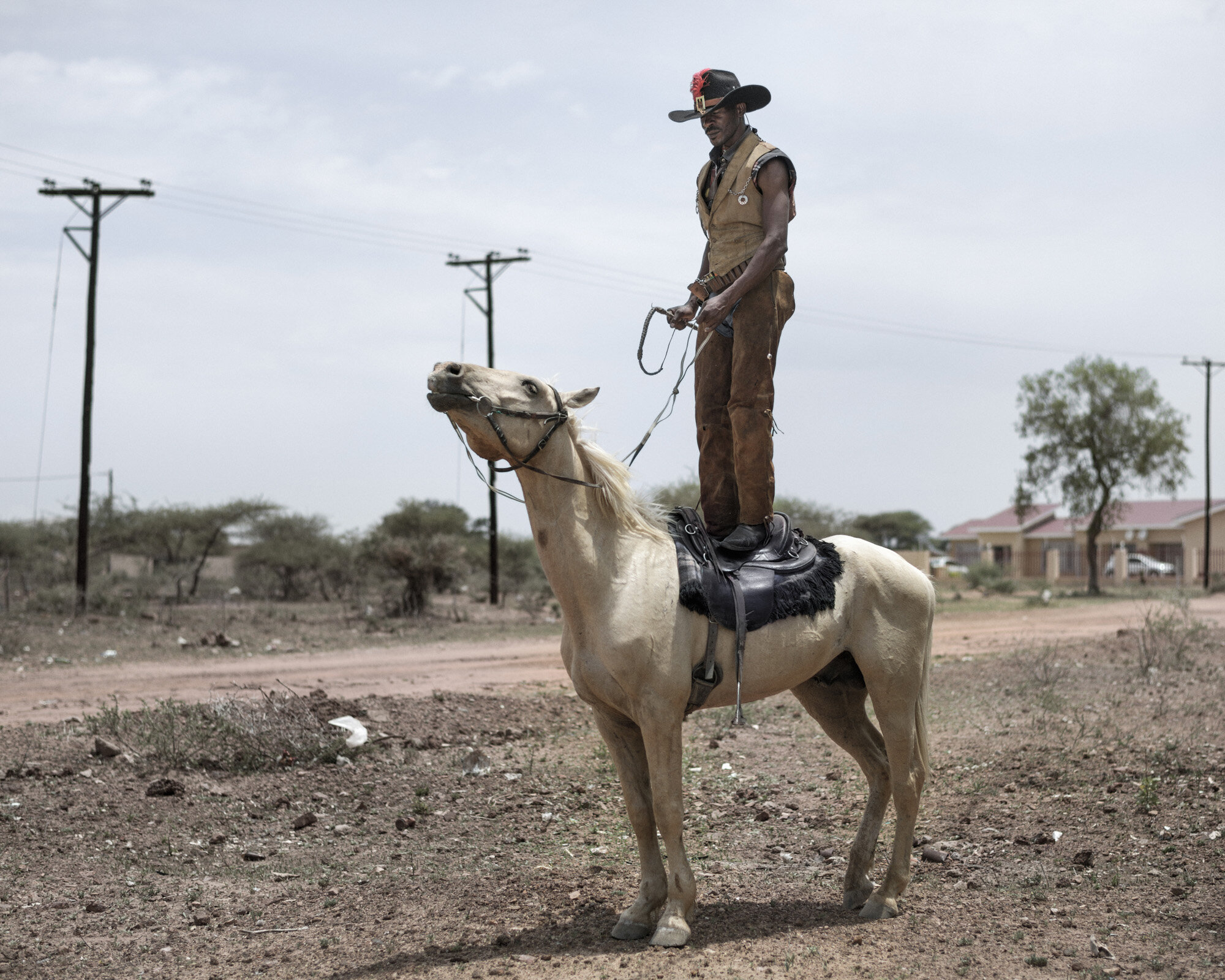 """Africa, Botswana, Gaborone, December 2015Photo by Pep Bonet / NOORPortrait of 38 years old """"King Taker""""I am a cowboy, I´m self employed and I deal with metal works such as welding and other stuff. I became a cowboy in 1993, I watched too much cowboy movies such as the good, bad and ugly and I was influenced, I wanted to be like them.  So in 2003 I became a brutal cowboy, I rode horses since at the age of 7 and half years, Im a cowboy who listen to metal because I love metal music, I have friends who are metal heads and I have spent the rest of my life in metal scene and attending shows, my favorite bands are Amon Amarth and Manowar. Today I was riding a Golden horse by the name Class."""