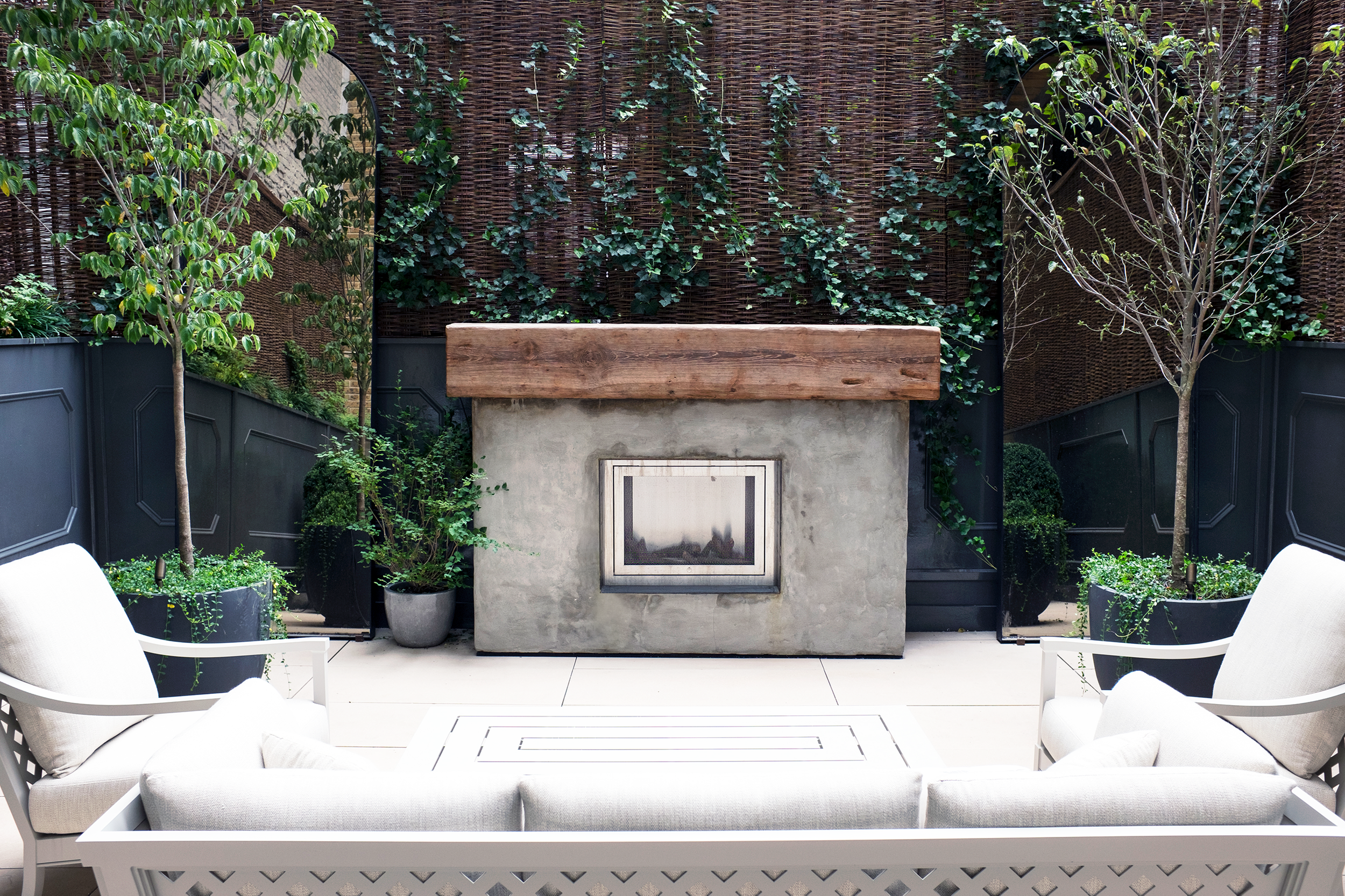 Union Square - Private Terrace : A photo showing the installation of a custom stucco fireplace with a reclaimed timber mantel and a custom panel wall with detail moldings.
