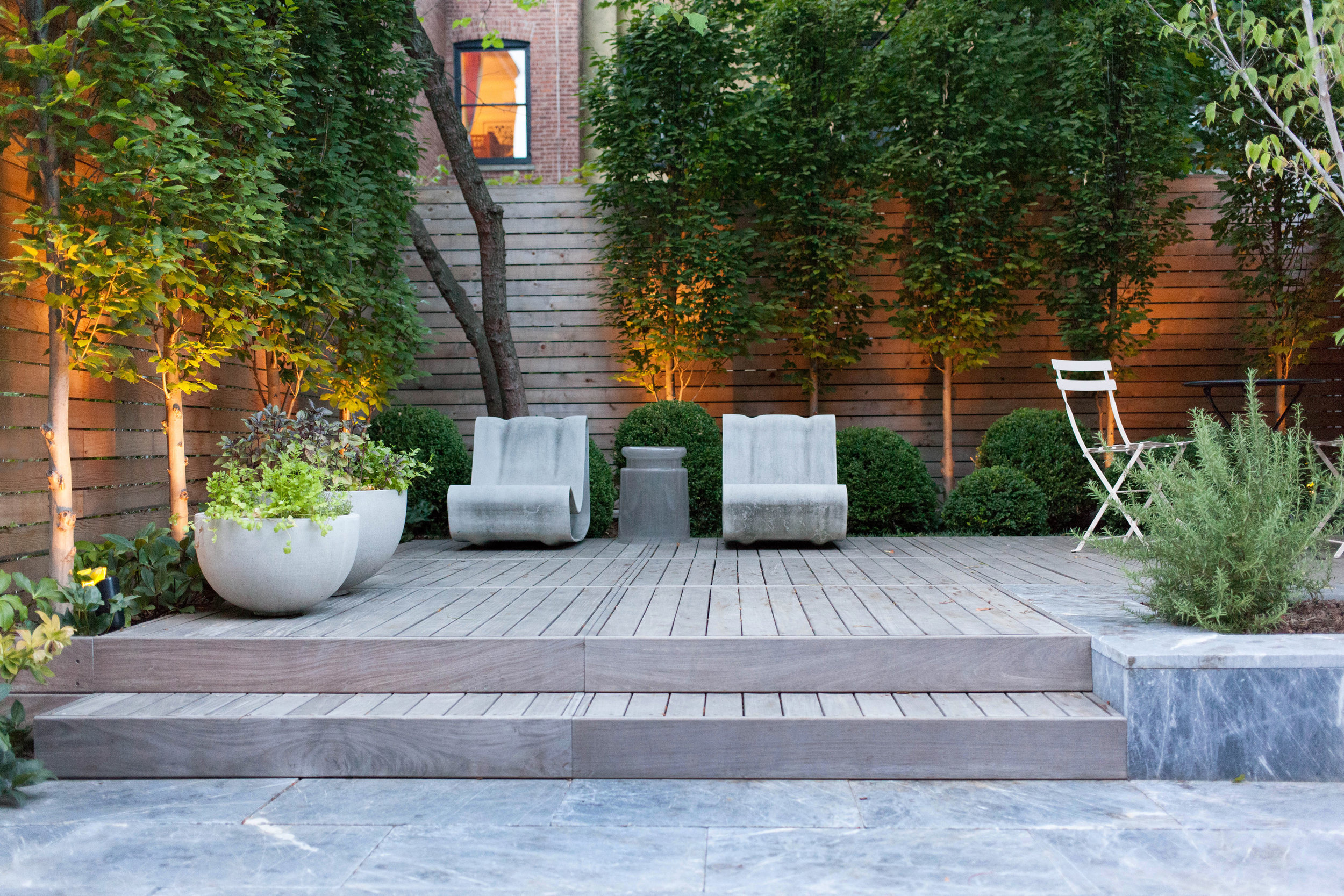 Midwood - Rear yard : A photo showing the installation of a marble patio and IPE deck with uplighting on hornbeams and a horizontal cedar fence.