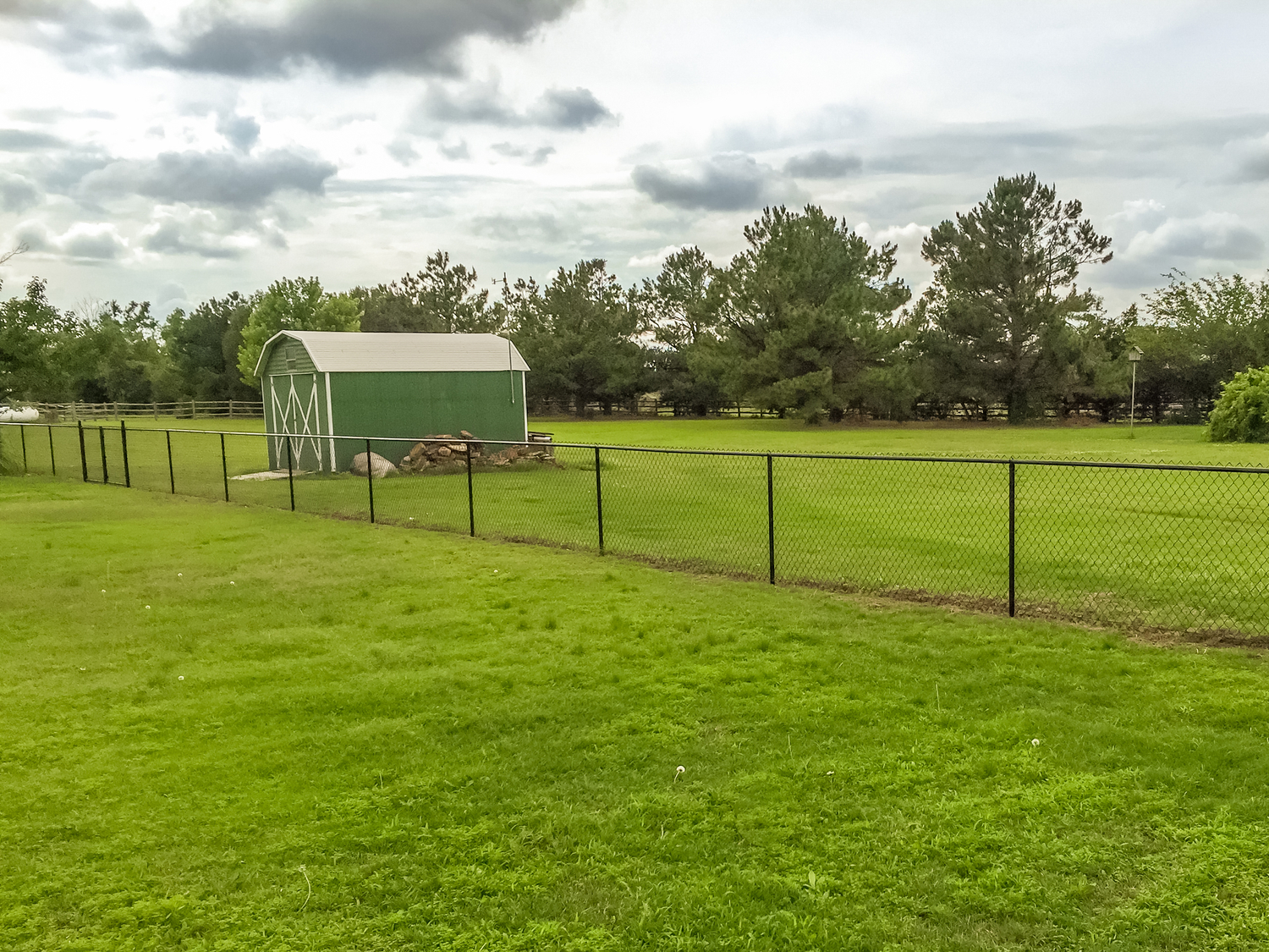 chain-link-black-vinyl-fence-barn-grass-field.jpg
